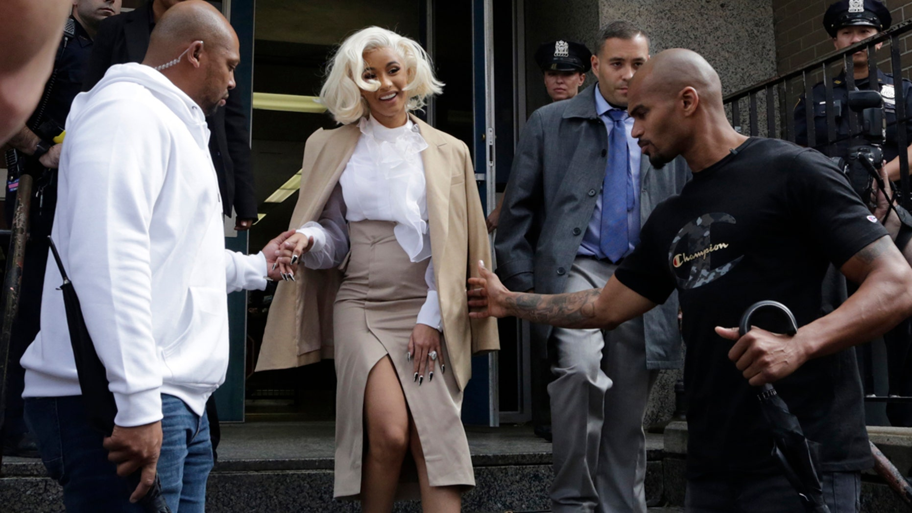 Rapper Cardi B is assisted by security guards as she leaves a police precinct Monday Oct. 1 2018 in the Queens borough of New York. The rapper met with police as part of an investigation of her possible involvement in a fight at a strip club