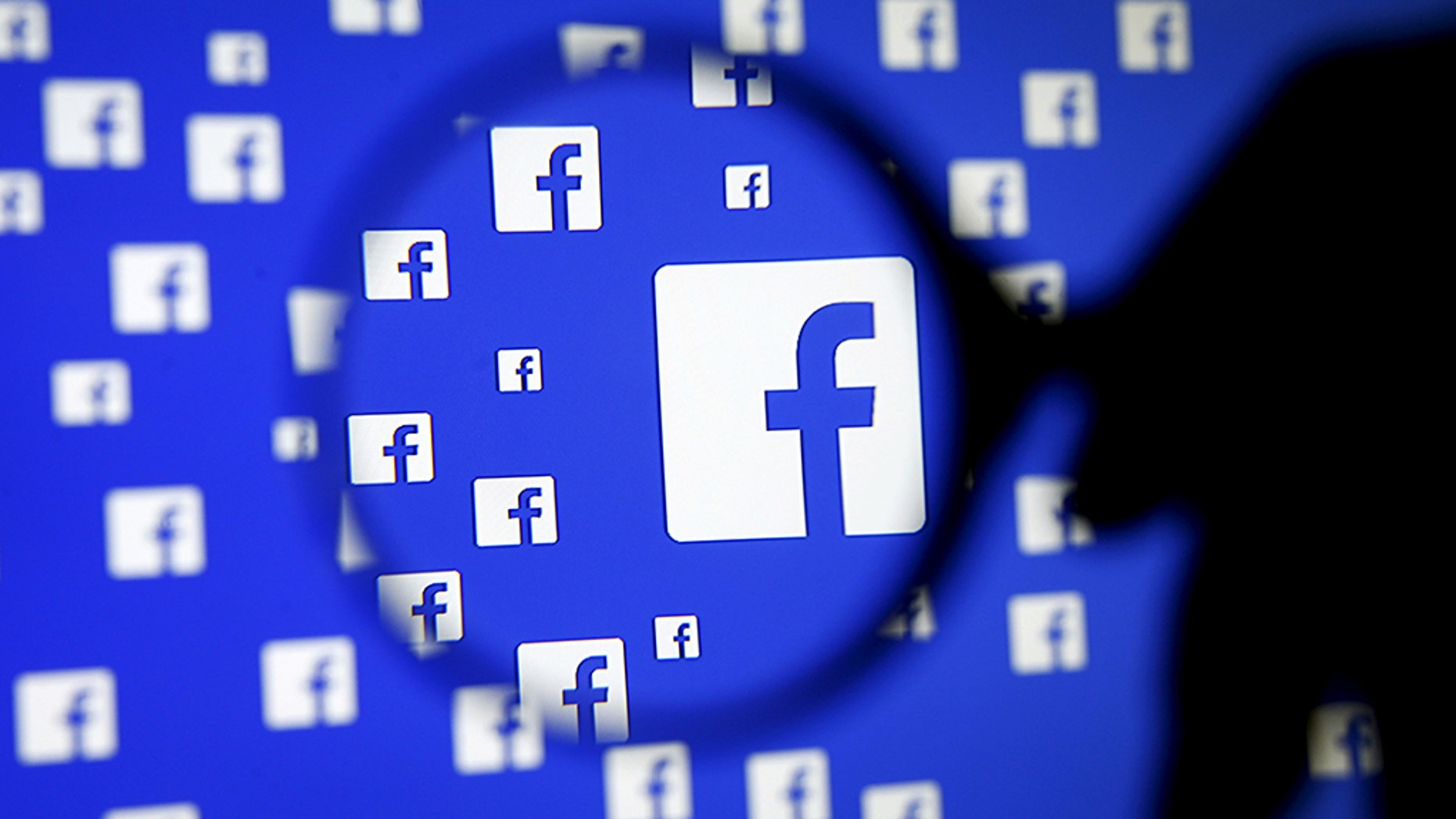 File photo: A man poses with a magnifier in front of a Facebook logo on display in this illustration taken in Sarajevo, Bosnia and Herzegovina, December 16, 2015. REUTERS/Dado Ruvic/Illustration