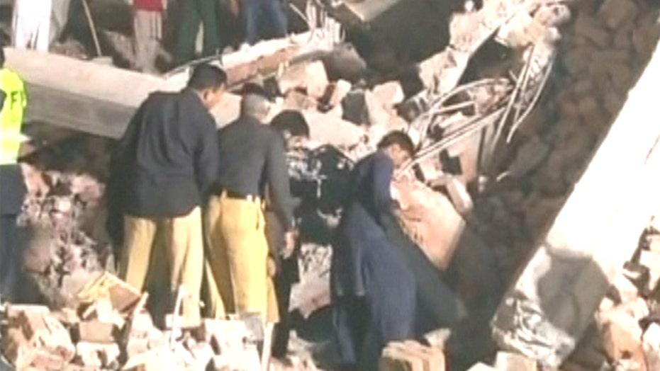Rescuers search rubble for survivors of building collapse
