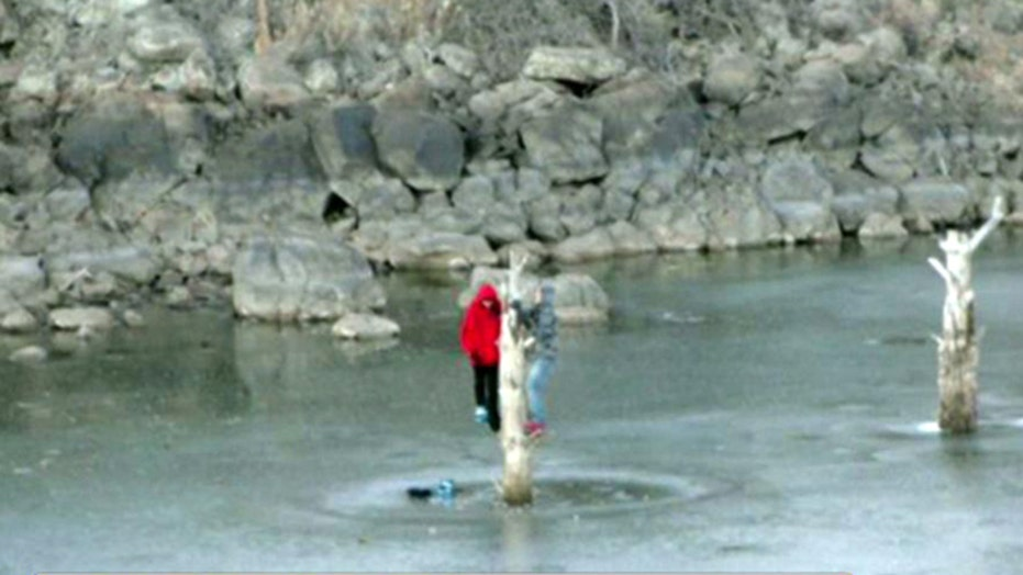 Teens trapped on icy lake cling to tree for four hours