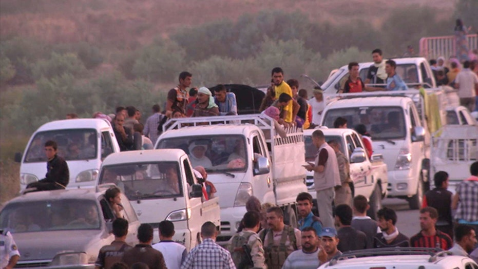 Thousands flee after ISIS militants seize towns in Iraq