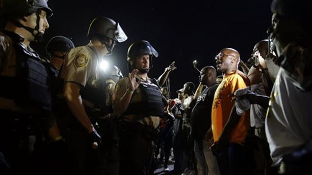 Officers and protesters face off in Ferguson, Mo., Aug. 10, 2015.