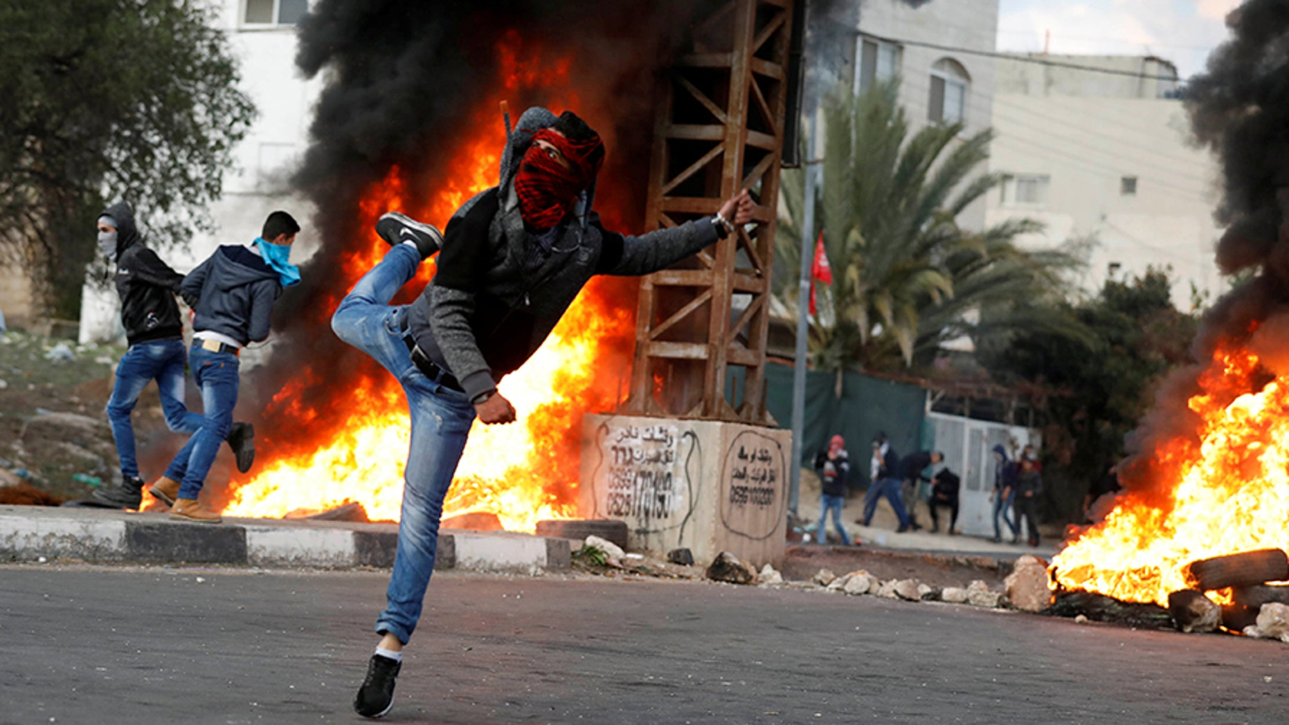 A Palestinian demonstrator hurls stones toward Israeli troops during clashes at a protest against U.S. President Donald Trump's decision to recognize Jerusalem as the capital of Israel, near the West Bank city of Nablus, December 29, 2017