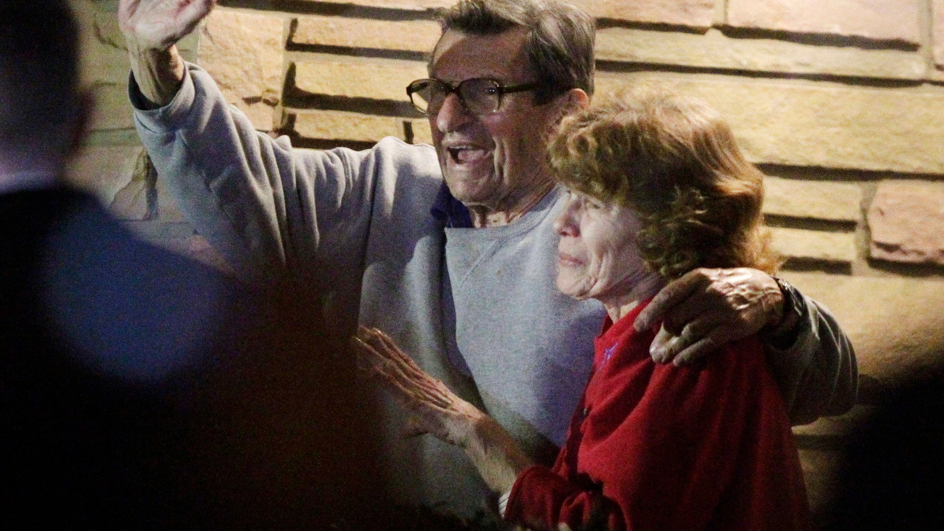FILE - In this Nov. 9, 2011 file photo, former Penn State Coach Joe Paterno and his wife, Sue Paterno, stand on their porch to thank supporters gathered outside their home in State College, Pa. Sue Paterno says the family's detailed response to a critical report on the handling of child abuse allegations against former assistant coach Jerry Sandusky is being released to the public. (AP Photo/Gene J. Puskar, File)