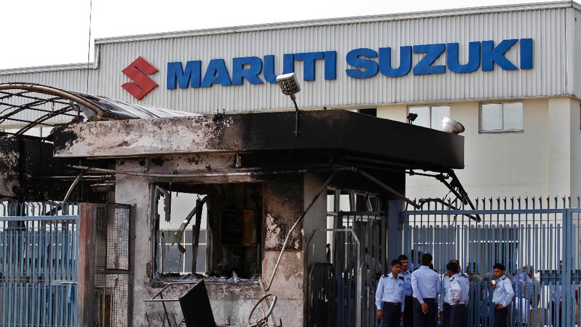 FILE - In this July 19, 2012, file photo, security guards stand near a burnt down reception block of Maruti Suzuki factory in Manesar, near New Delhi, India. A court in north India has sentenced 13 factory workers to life imprisonment for taking part in violence at the country's largest automobile factory that led to the death of a manager nearly five years ago. (AP Photo/Saurabh Das, File)