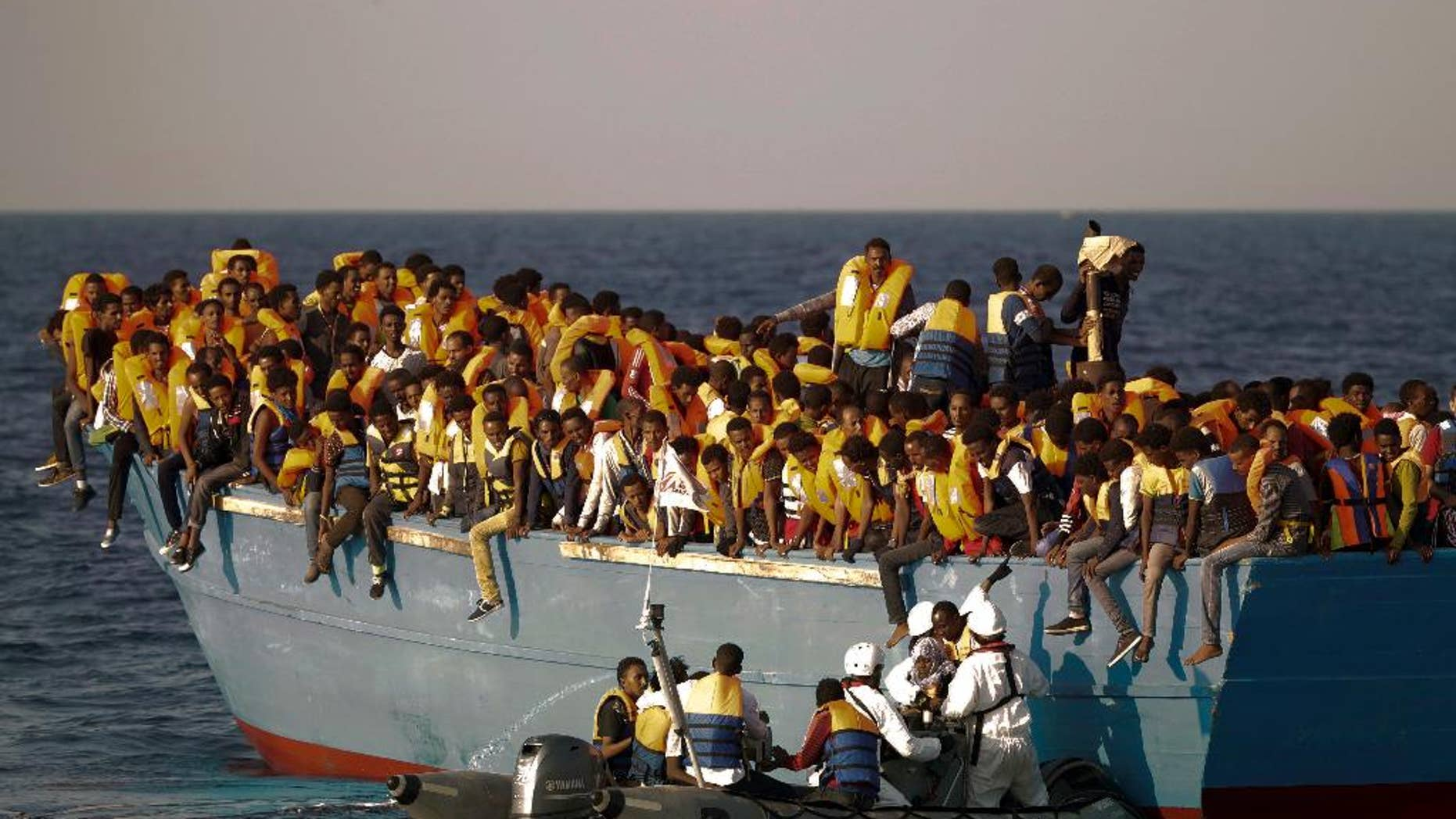 """FILE - In this Monday, Aug. 29, 2016 file photo, migrants crowd onto a wooden boat as they wait to be rescued by members of an ONG at the Mediterranean sea, about 13 miles north of Sabratha, Libya. When the camera's viewfinder is in """"night vision"""" mode, a hidden world appears that is invisible to the naked eye in the darkness of night. Bathed in green, the view is even more dreamlike _ or nightmarish.  (AP Photo/Emilio Morenatti, File)"""