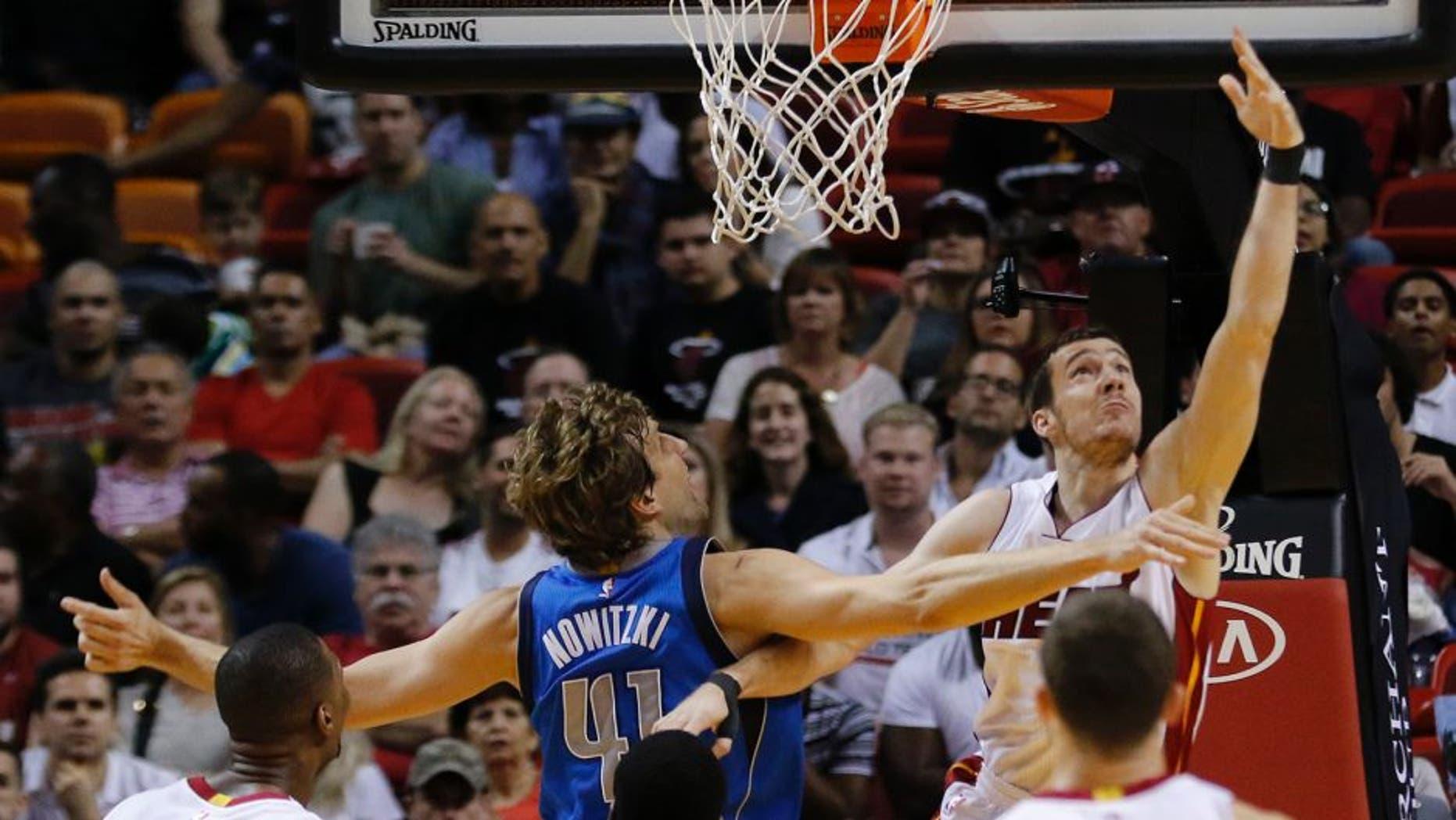 Miami Heat guard Goran Dragic (7) shoots as Dallas Mavericks forward Dirk Nowitzki (41) defends during the first half of an NBA basketball game, Friday, Jan. 1, 2016, in Miami. (AP Photo/Joe Skipper)