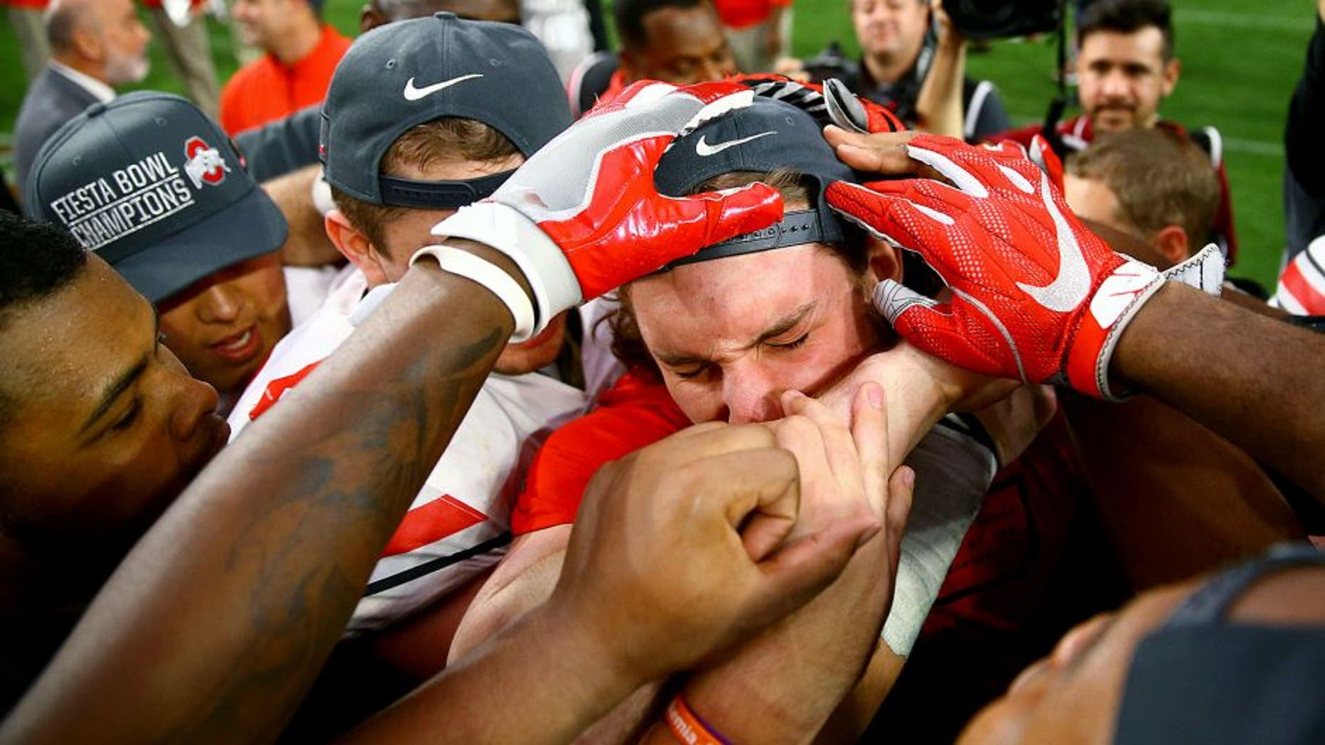 Jan 1, 2016; Glendale, AZ, USA; Ohio State Buckeyes defensive lineman Joey Bosa reacts as he celebrates with teammates on the field following the game against the Notre Dame Fighting Irish during the 2016 Fiesta Bowl at University of Phoenix Stadium. The Buckeyes defeated the Fighting Irish 44-28. Bosa was ejected in the first quarter for targeting. Mandatory Credit: Mark J. Rebilas-USA TODAY Sports