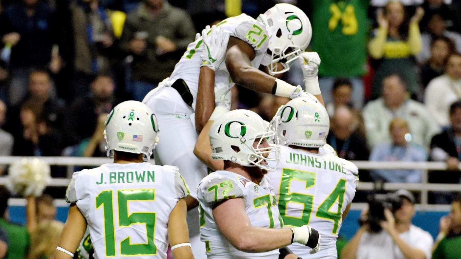 Jan 2, 2016; San Antonio, TX, USA; Oregon Ducks running back Royce Freeman (21) is hoisted by teammates after scoring on a 4-yard touchdown run against the TCU Horned Frogs during the 2016 Alamo Bowl at Alamodome. Mandatory Credit: Kirby Lee-USA TODAY Sports