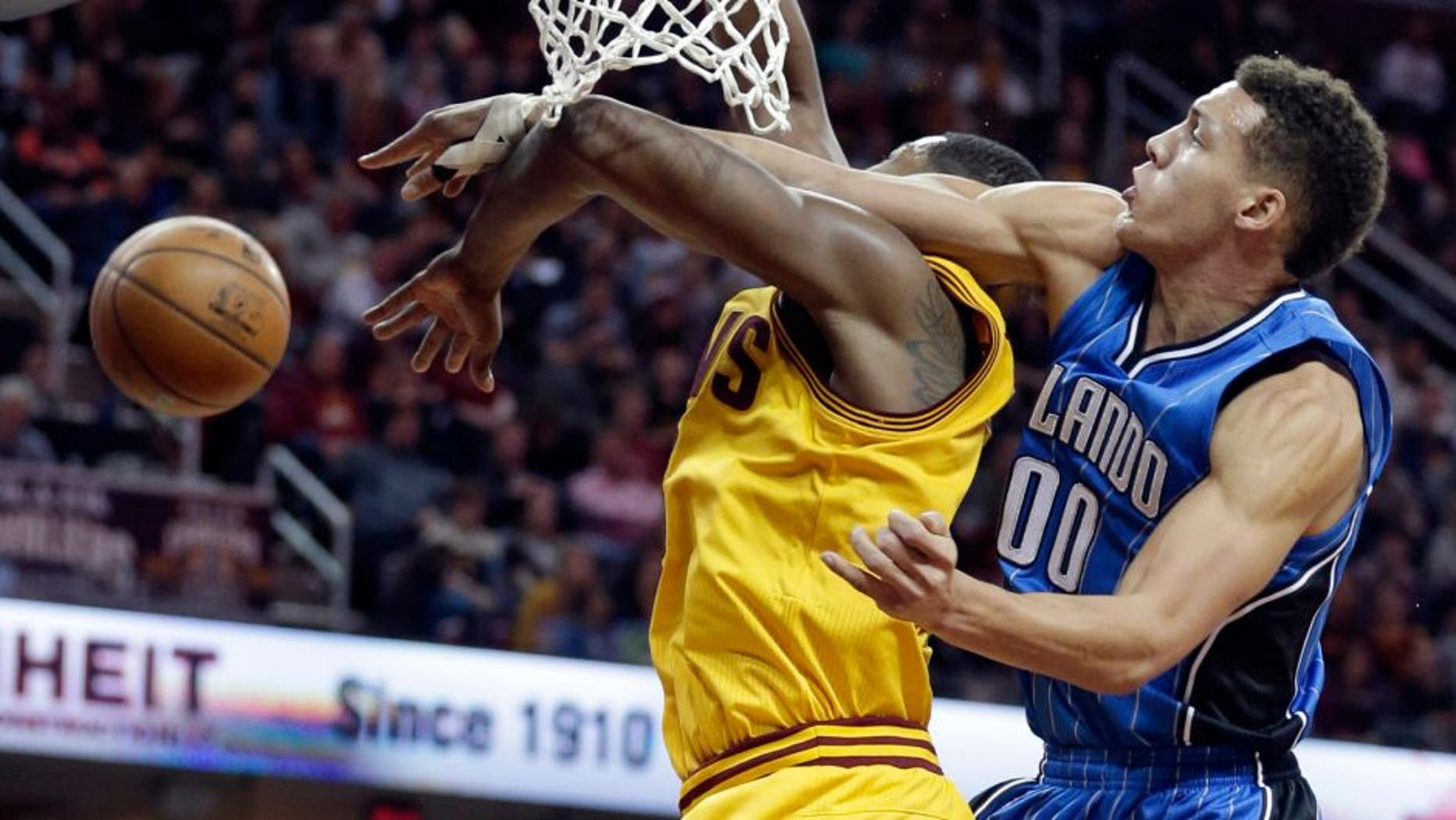 Orlando Magic's Aaron Gordon, right, knocks the ball loose from Cleveland Cavaliers' Tristan Thompson, from Canada, in the first half of an NBA basketball game Saturday, Jan. 2, 2016, in Cleveland. (AP Photo/Tony Dejak)