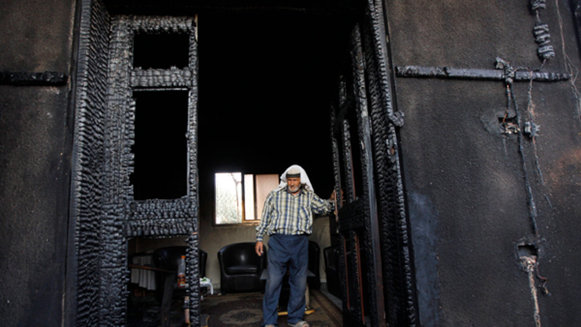 FILE - In this July 31, 2015 file photo, a Palestinian inspects a house after it was torched in a suspected attack by Jewish settlers, killing an 18-month-old Palestinian child and his parents, at Duma village near the West Bank city of Nablus.