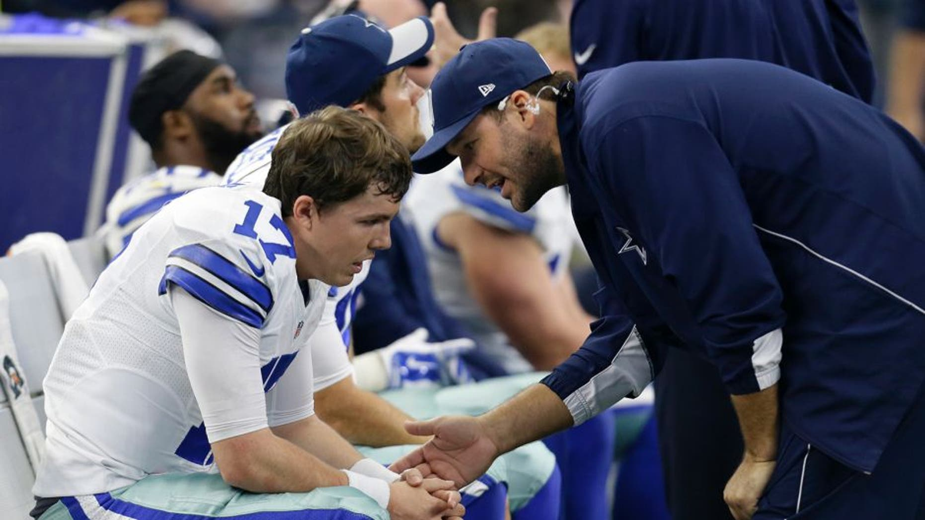 Dallas Cowboys quarterback Kellen Moore, left, talks with injured quarterback Tony Romo, right, in the second half of an NFL football game against the Washington Redskins on Sunday, Jan. 3, 2016, in Arlington, Texas. (AP Photo/Tim Sharp)