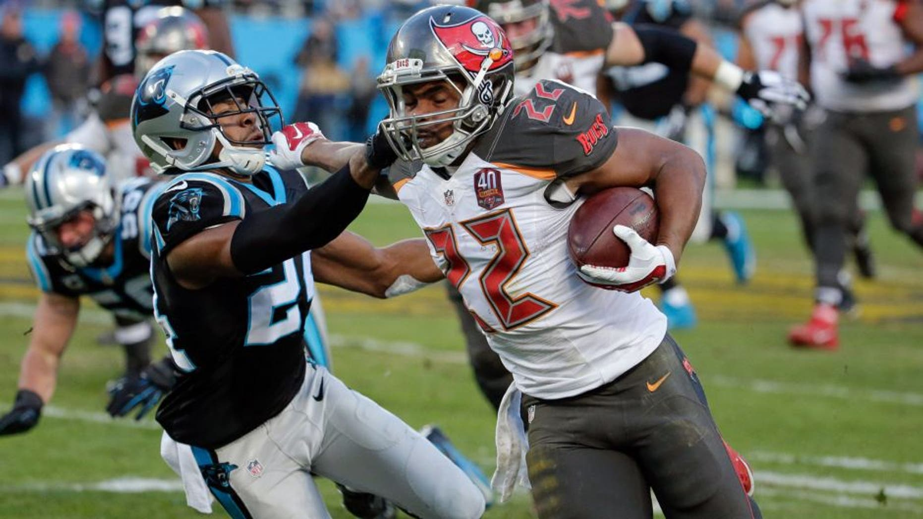 Jan 3, 2016; Charlotte, NC, USA; Tampa Bay Buccaneers running back Doug Martin (22) stiff arms Carolina Panthers cornerback Josh Norman (24) during the second quarter at Bank of America Stadium. Mandatory Credit: Jeremy Brevard-USA TODAY Sports