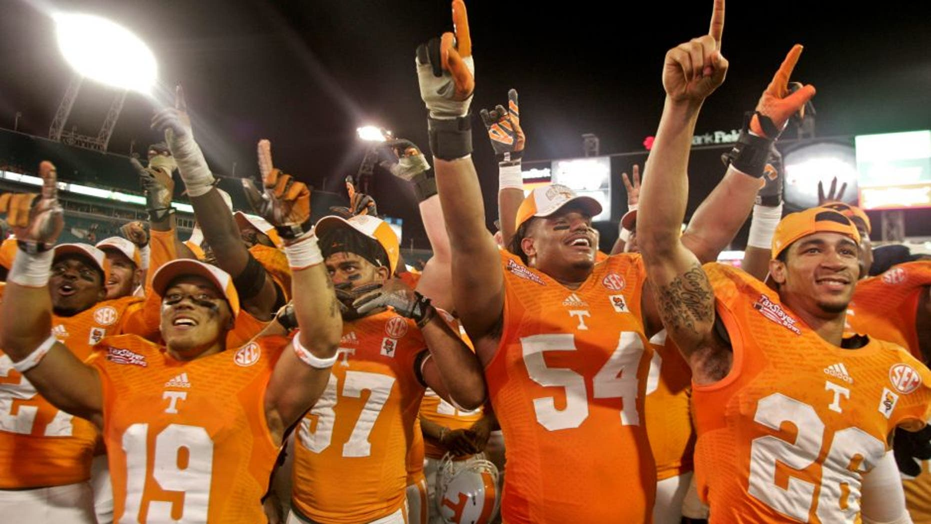 Jan 2, 2015; Jacksonville, FL, USA; Tennessee Volunteers running back Devrin Young (19) and defensive back Brian Randolph (37) and defensive tackle Jordan Williams (54) and defensive back Geraldo Orta (26) celebrate with fans after their 2015 TaxSlayer Bowl game against the Iowa Hawkeyes at EverBank Field. The Tennessee Volunteers beat the Iowa Hawkeyes 45-28. Mandatory Credit: Phil Sears-USA TODAY Sports