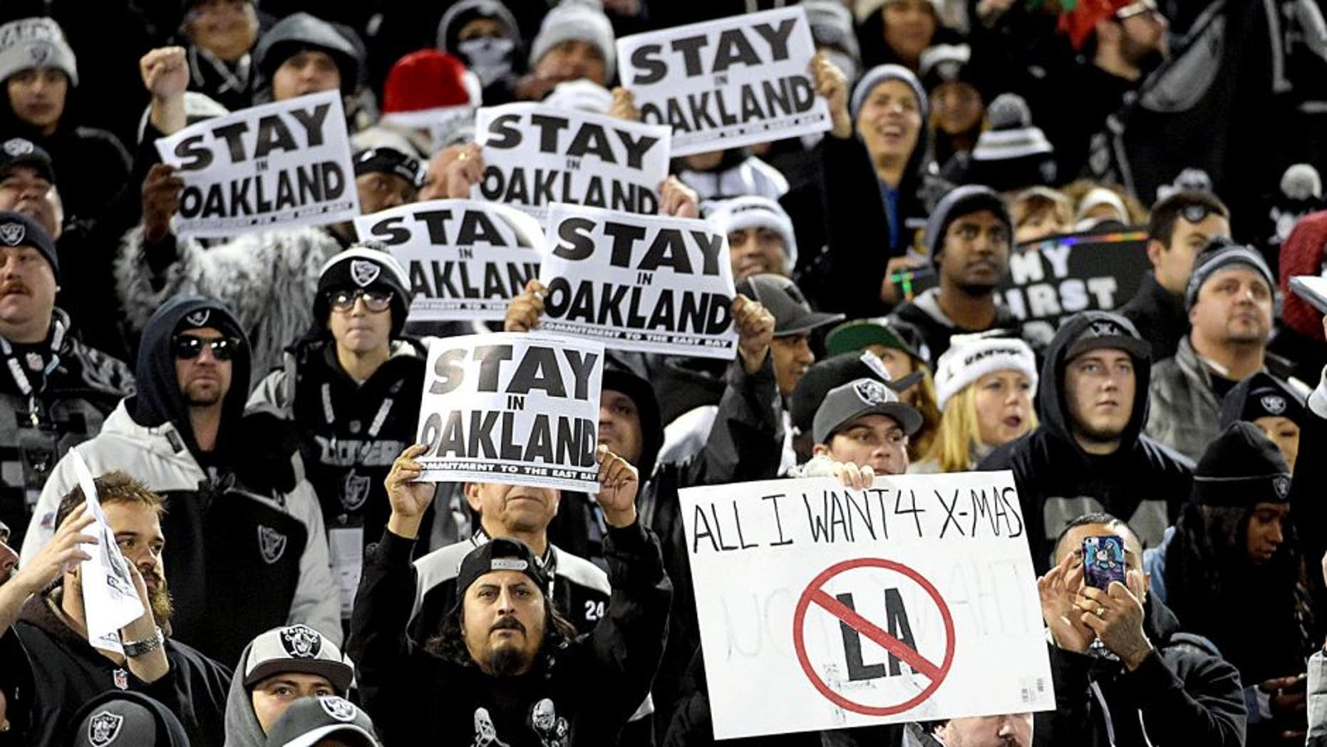 """Dec 24, 2015; Oakland, CA, USA; Oakland Raiders fans hold signs that read """"Stay in Oakland"""" in opposition of the Raiders potential move to Los Angeles during an NFL football game against the San Diego Chargers at O.co Coliseum. Mandatory Credit: Kirby Lee-USA TODAY Sports"""
