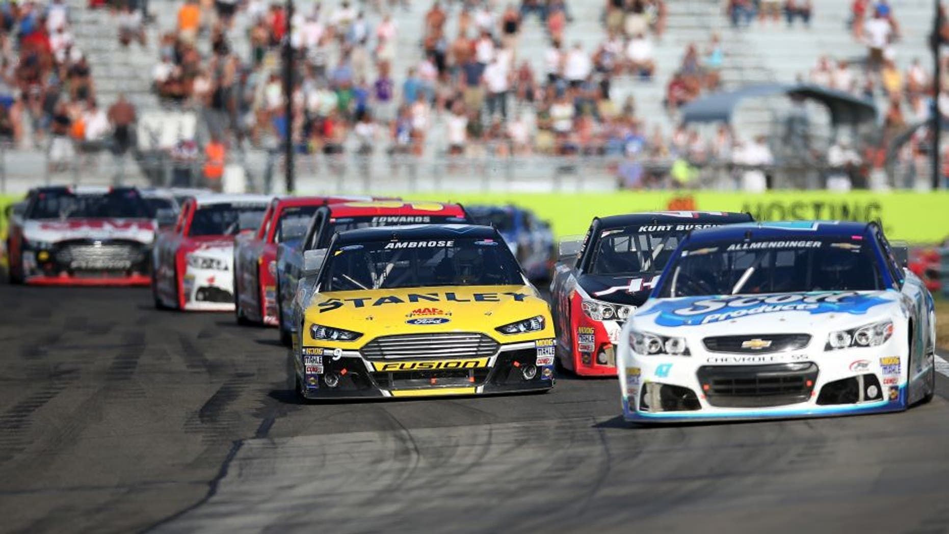 WATKINS GLEN, NY - AUGUST 10: AJ Allmendinger, driver of the #47 Scott Products Chevrolet, leads Marcos Ambrose, driver of the #9 Stanley Ford, and the field during the NASCAR Sprint Cup Series Cheez-It 355 at Watkins Glen International on August 10, 2014 in Watkins Glen, New York. (Photo by Chris Graythen/NASCAR via Getty Images)