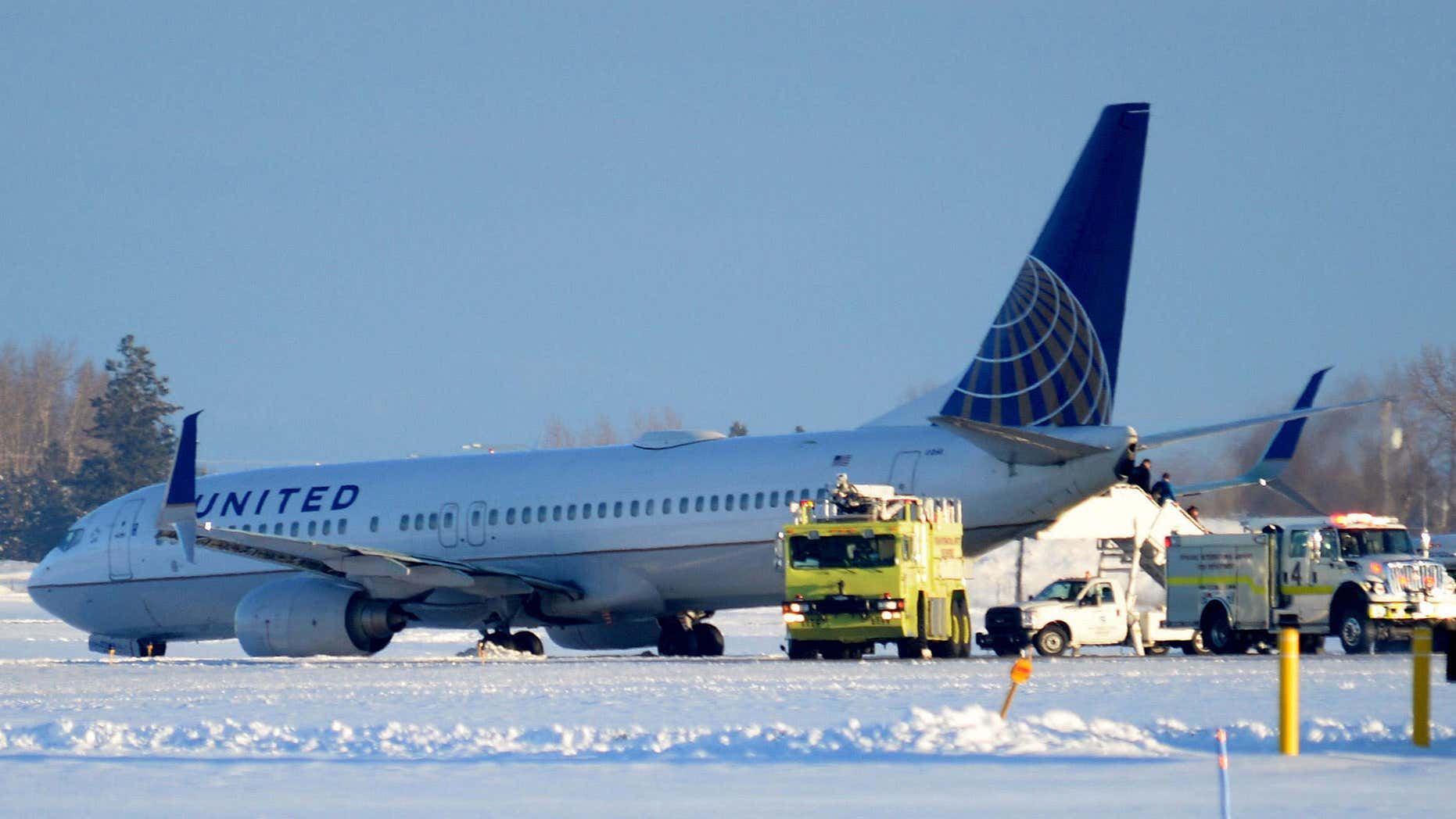 Jan. 5, 2016: Emergency vehicles surround a United Airlines aircraft as passengers wait to be evacuated at the Spokane International Airport in Spokane, Wash.