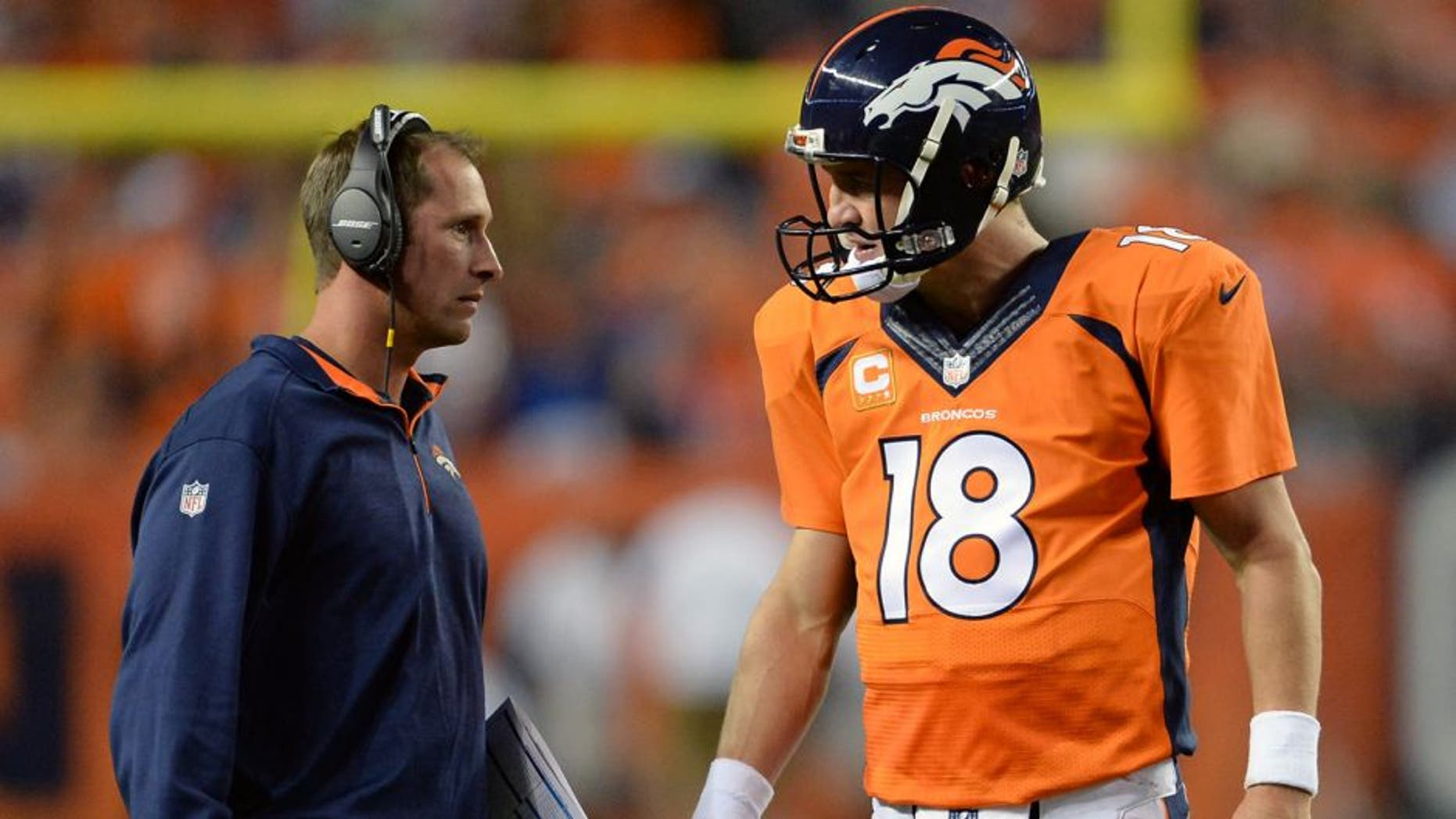 Sep 7, 2014; Denver, CO, USA; Denver Broncos offensive coordinator Adam Gase and quarterback Peyton Manning (18) speak in the second quarter against the Indianapolis Colts at Sports Authority Field at Mile High. The Broncos defeated the Colts 31-24. Mandatory Credit: Ron Chenoy-USA TODAY Sports