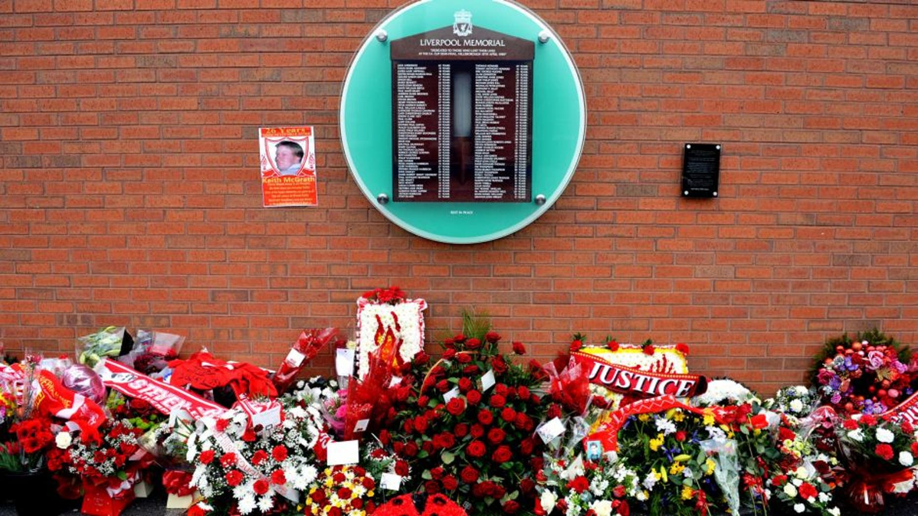 Flowers sit beneath the temporary Hillsborough memorial, ahead of a memorial service at Anfield in Liverpool, north west Engand on April 15, 2015, on the 26th anniversary of the Hillsborough Disaster, where 96 Liverpool supporters died at the 1989 FA Cup semi final between Liverpool and Nottingham Forest at Hillsborough football ground in Sheffield. AFP PHOTO / PAUL ELLIS (Photo credit should read PAUL ELLIS/AFP/Getty Images)
