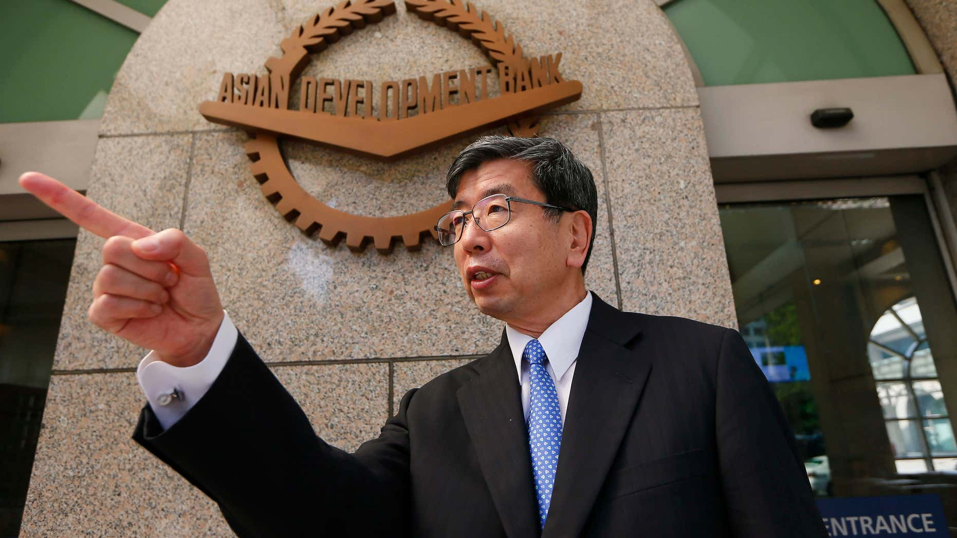 Jan. 8, 2016: Asian Development Bank President Takehiko Nakao gestures to an aide in front of the logo at the financial institution's headquarters following a forum with foreign correspondents based in the Philippines at suburban Mandaluyong city east of Manila, Philippines.