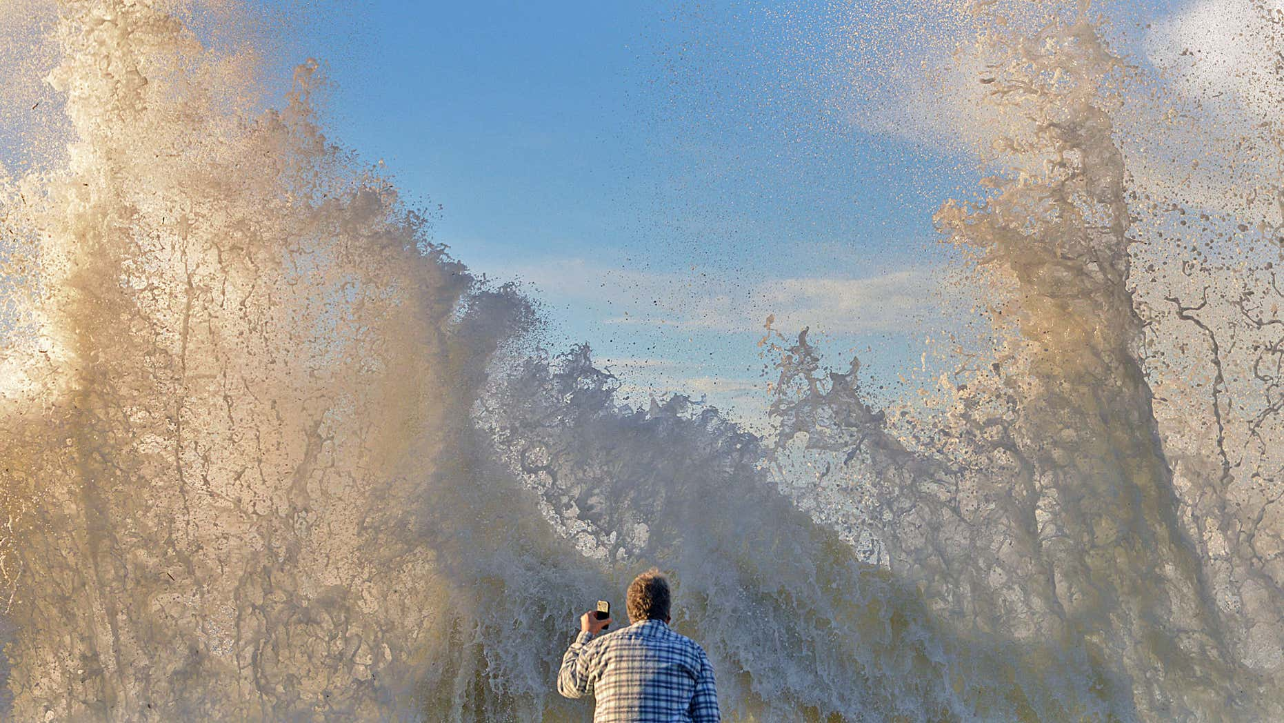 Jan. 7, 2016: In a photo provided by Mike Eliason, Bo Sailor of Goleta, Caif. watches as high surf crashes into the wall and spills onto Channel Drive in Montecito, Calif.