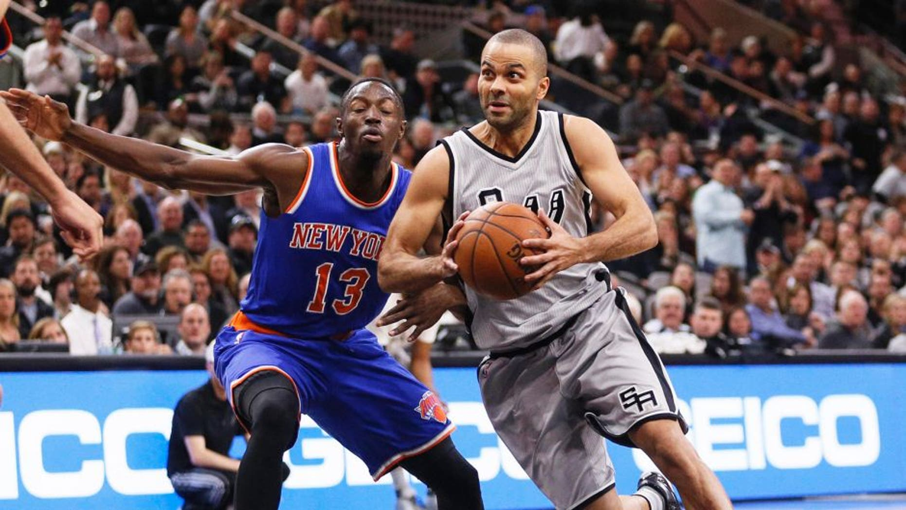 Jan 8, 2016; San Antonio, TX, USA; San Antonio Spurs point guard Tony Parker (right) drives to the basket around New York Knicks point guard Jerian Grant (13) during the first half at AT&T Center. Mandatory Credit: Soobum Im-USA TODAY Sports