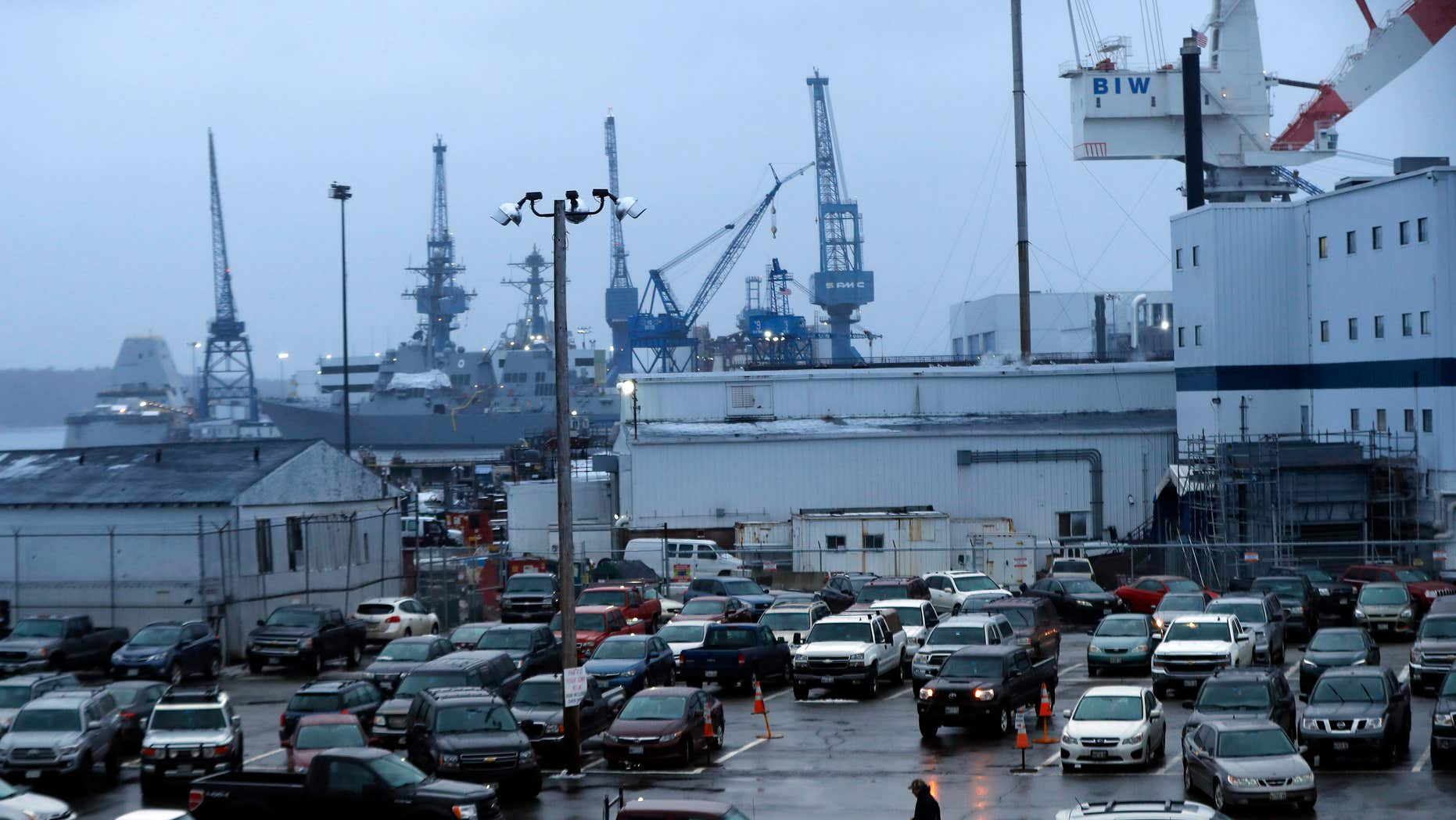 In this Tuesday, Jan. 3, 2017 photo, a shipyard worker walks to his car at the end of the workday at Bath Iron Works in Bath, Maine.