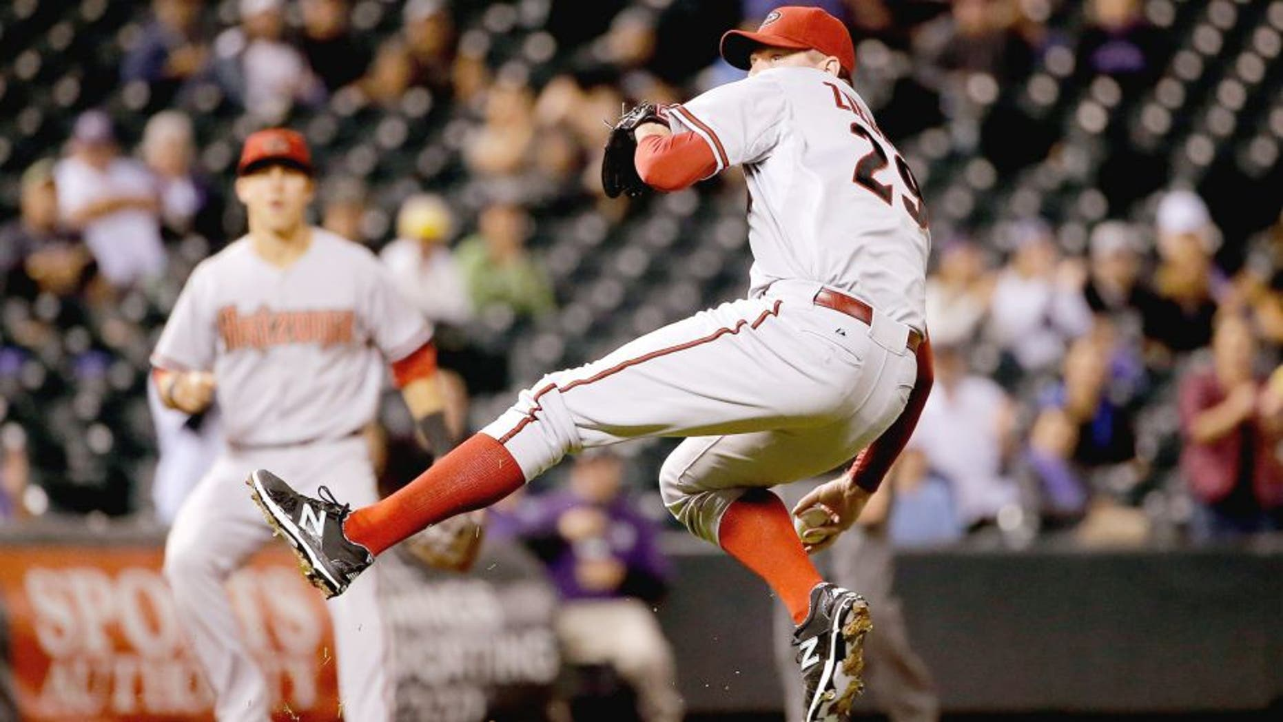 DENVER, CO - AUGUST 31: Relief pitcher Brad Ziegler #29 of the Arizona Diamondbacks makes a throwing error after fielding a ground ball by DJ LeMahieu #9 of the Colorado Rockies in the ninth inning at Coors Field on August 31, 2015 in Denver, Colorado. Ziegler would collect the loss as the Rockies defeated the Diamondbacks 5-4. (Photo by Doug Pensinger/Getty Images)