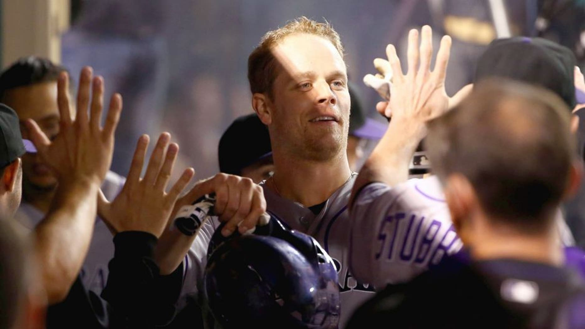 ANAHEIM, CA - MAY 12: Justin Morneau #33 of the Colorado Rockies celebrates in the dugout after scoring on Corey Dickerson's rbi double to deep right field in the fourth inning during the MLB game against the Los Angeles Angels of Anaheim at Angel Stadium of Anaheim on May 12, 2015 in Anaheim, California. The Angels defeated the Rockies 5-2. (Photo by Victor Decolongon/Getty Images)