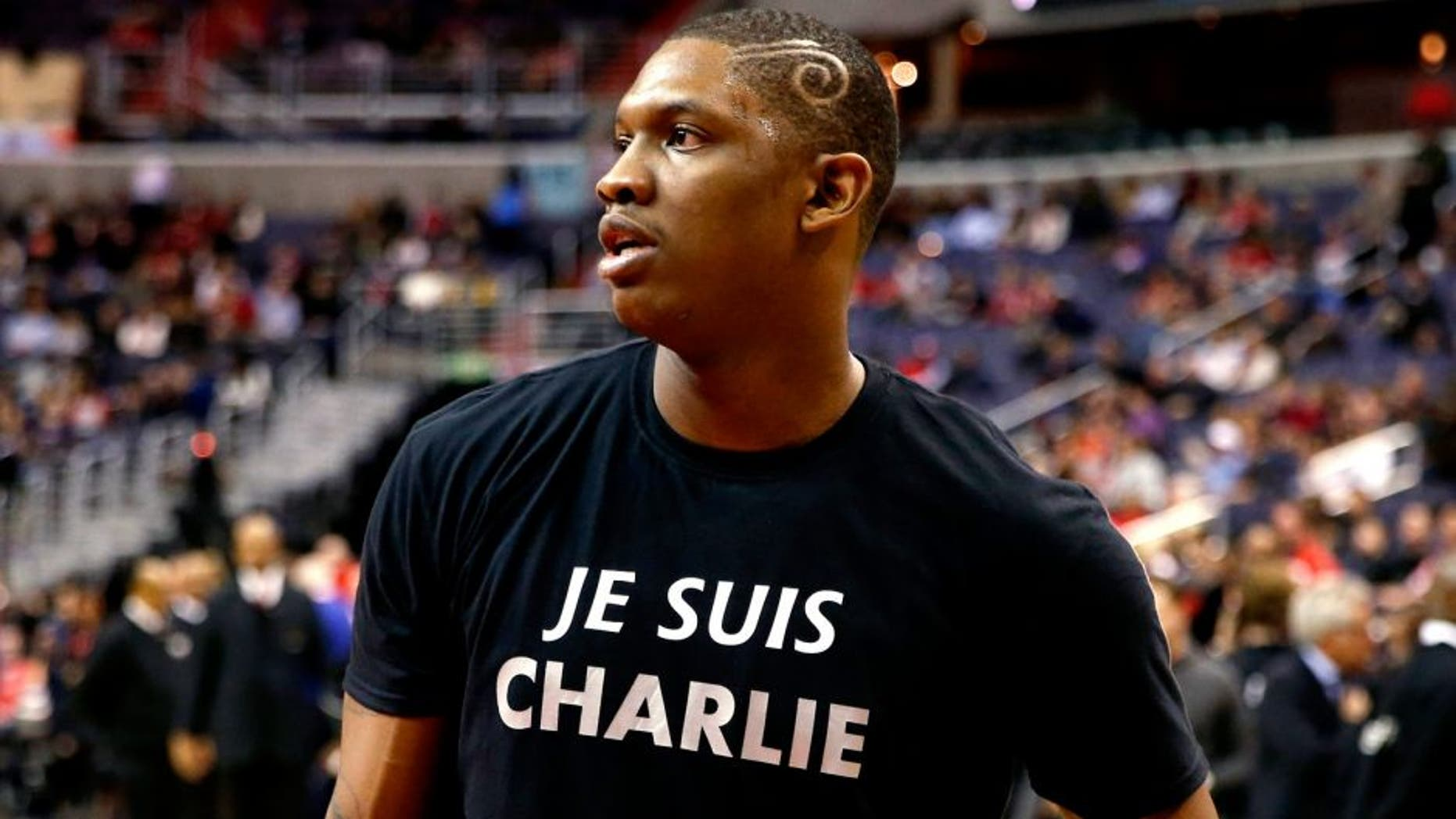 """Washington Wizards center Kevin Seraphin, from France, wears a """"Je Suis Charlie"""" T-shirt during warmups for an NBA basketball game against the Chicago Bulls, Friday, Jan. 9, 2015, in Washington. """"Je Suis Charlie"""" ó """"I Am Charlie"""" in English ó has become a worldwide slogan to show solidarity with Charlie Hebdo, a Paris weekly newspaper where 12 people were killed Wednesday in a terrorist attack. Seraphin was born in French Guiana and has represented France in international competitions. (AP Photo/Alex Brandon)"""
