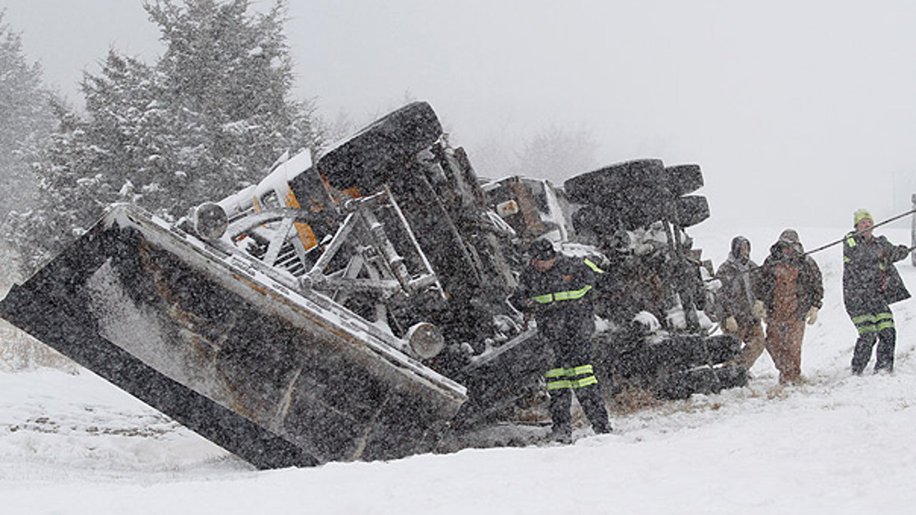 Jan 10: A Douglas County, Kansas, snowplow flips over on an interstate amid an unusually cold storm (AP).