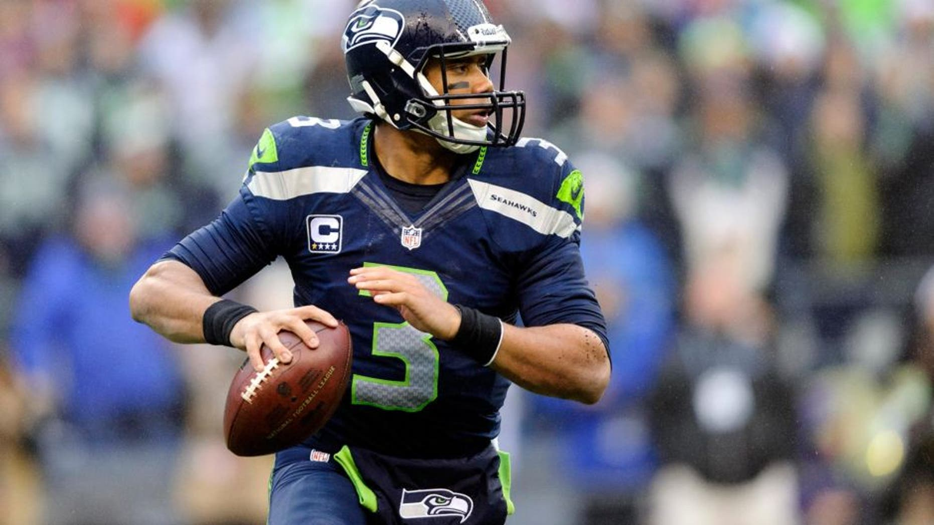 Dec 22, 2013; Seattle, WA, USA; Seattle Seahawks quarterback Russell Wilson (3) looks looks for an open receiver during the first half against the Arizona Cardinals at CenturyLink Field. Mandatory Credit: Steven Bisig-USA TODAY Sports