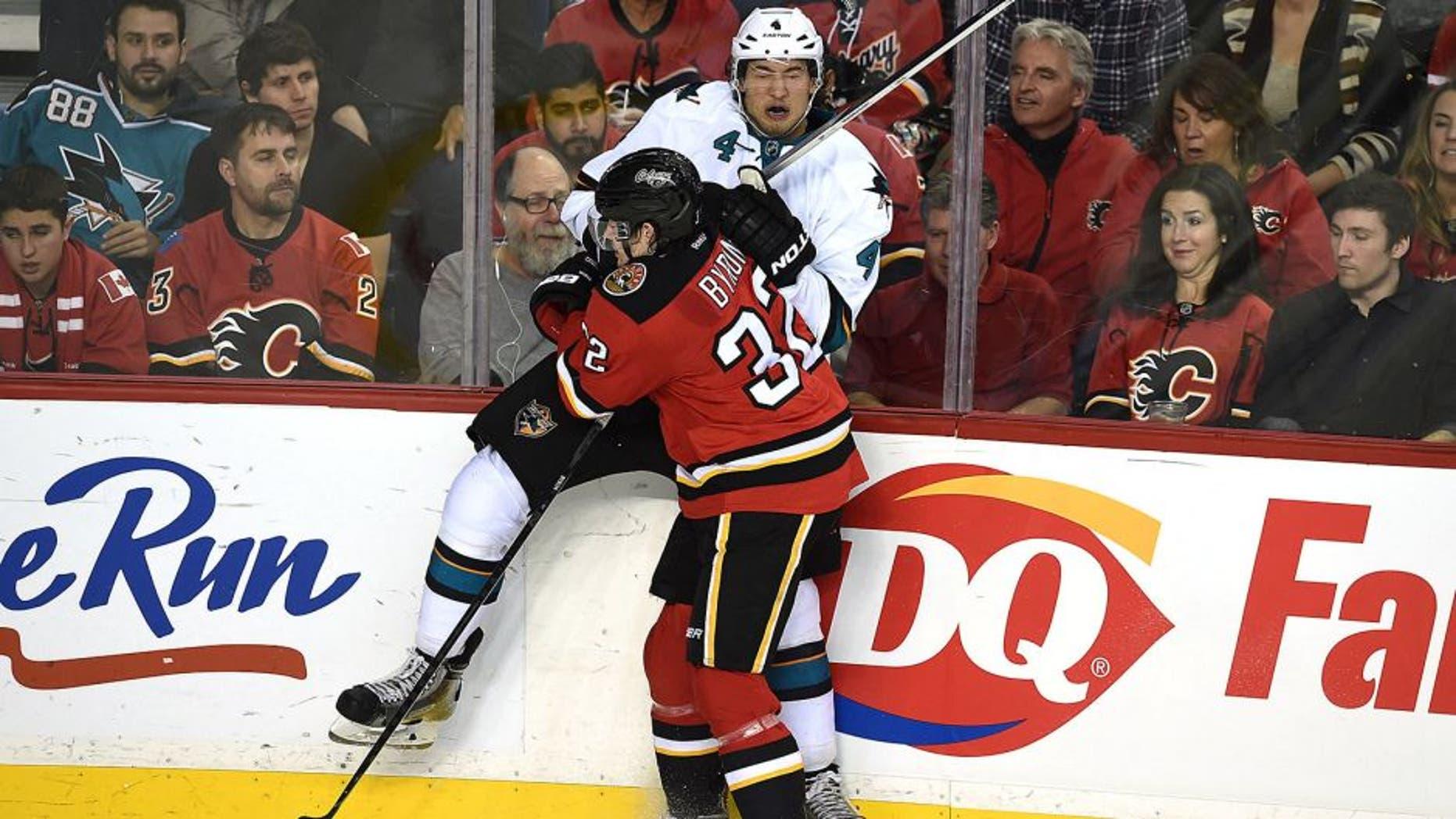 Dec 6, 2014; Calgary, Alberta, CAN; Calgary Flames center Paul Byron (32) checks San Jose Sharks defenseman Brenden Dillon (4) at Scotiabank Saddledome. Sharks won 3-2. Mandatory Credit: Candice Ward-USA TODAY Sports