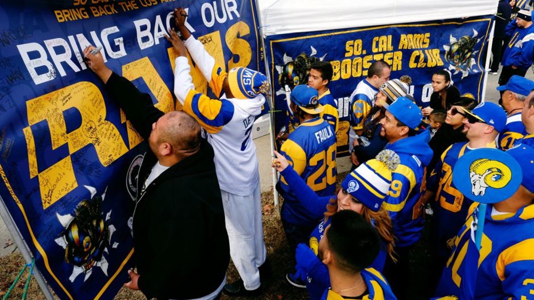 Rams fans sign a banner in support of their team at the historic Los Angeles Memorial Coliseum. Saturday, Jan. 9, 2016 in Los Angeles. Boisterous Los Angeles Rams fans gathered Saturday to herald the NFL football team's possibly imminent return to Southern California after a 21-year sojourn in St. Louis. (AP Photo/Richard Vogel)