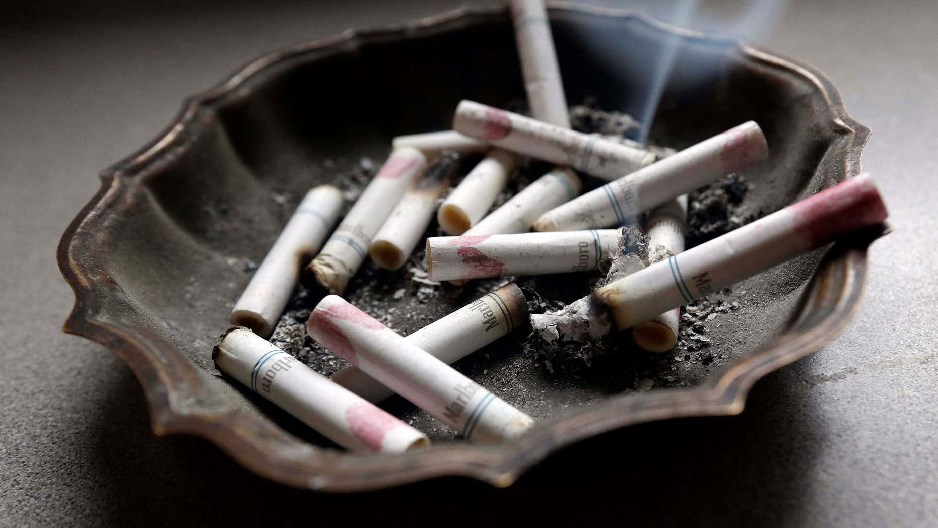 FILE - In this Saturday, March 2, 2013, photo, a cigarette burns in an ashtray at a home in Hayneville, Ala.