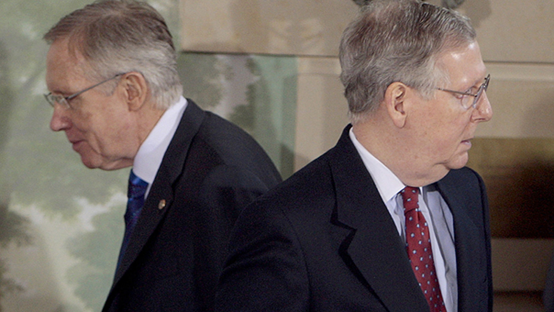 In this Feb. 25, 2010, file photo Senate Majority Leader Harry Reid of Nev., left, walks past Senate Minority Leader Mitch McConnell of Ky., during a meeting at the Blair House in Washington.