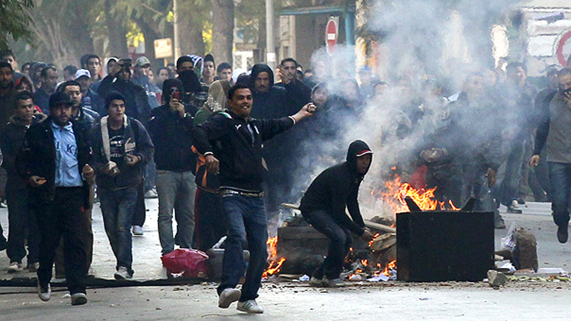 Jan. 14: Demonstrators throws stones at police during clashes in Tunis.