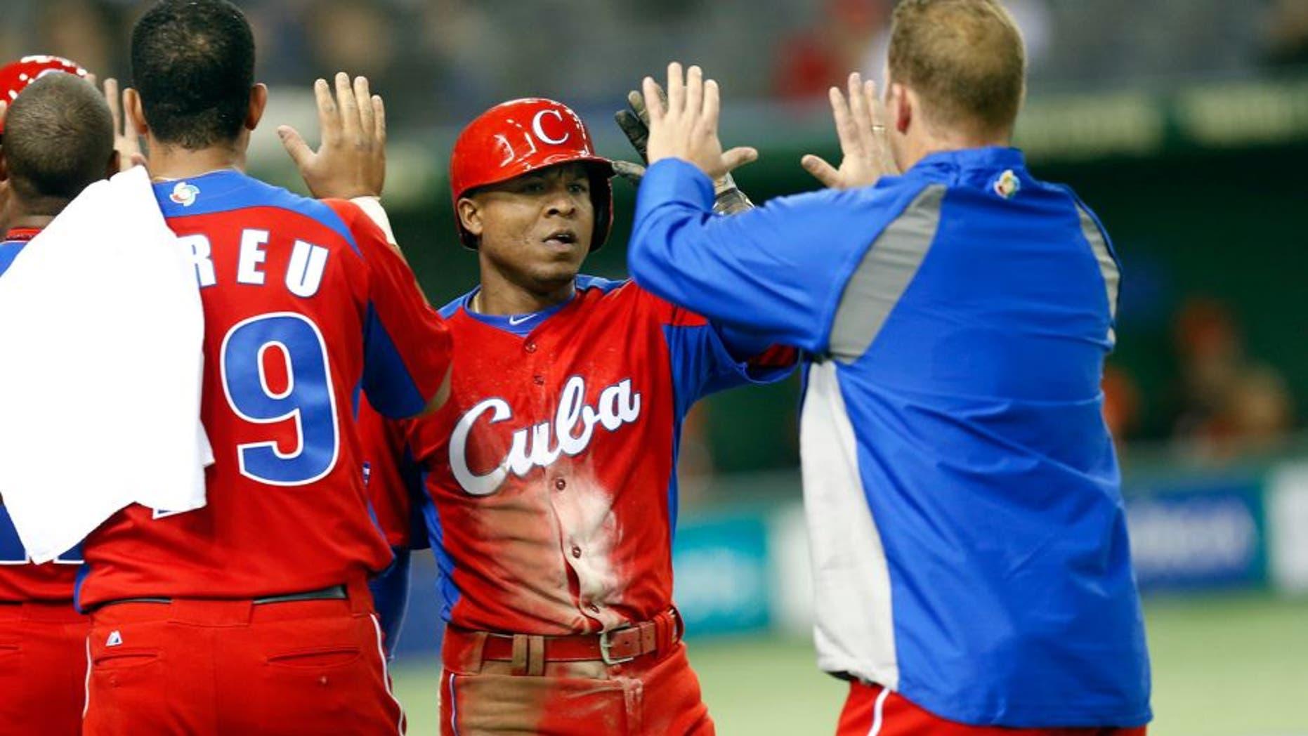 TOKYO, JAPAN - MARCH 11: Alexei Bell #88 of Team Cuba is greeted by teammates after scoring a run in the top of the fifth inning during action against Team Netherlands Pool 1, Game 5 in the second round of the 2013 World Baseball Classic at the Tokyo Dome on March 11, 2013 in Tokyo, Japan. (Photo by Yuki Taguchi/WBCI/MLB Photos via Getty Images)