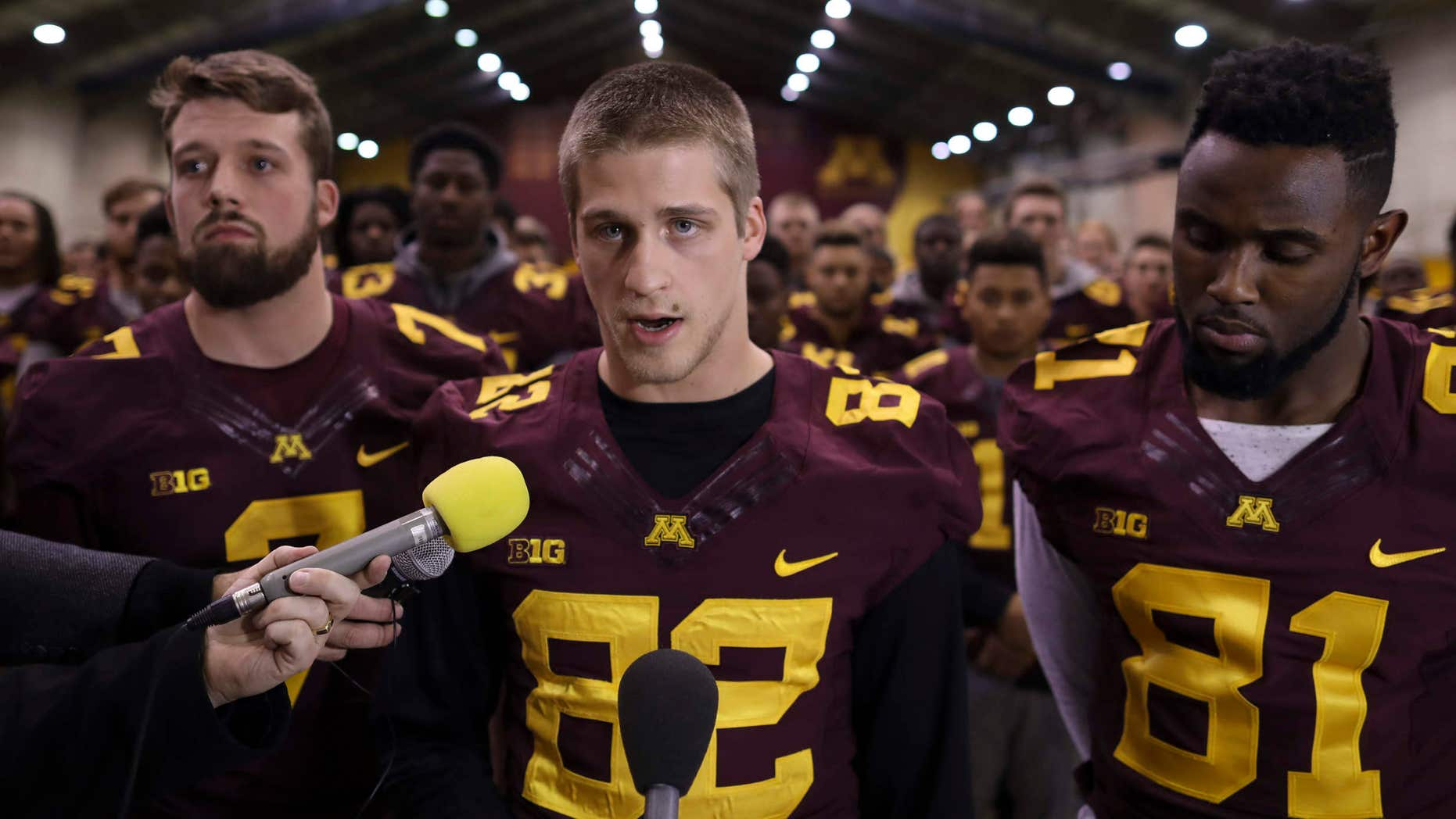 FILE - In this Dec. 15, 2016, file photo, University of Minnesota wide receiver Drew Wolitarsky, flanked by quarterback Mitch Leidner, left, and tight end Duke Anyanwu stands in front of other team members as he reads a statement on behalf of the players in the Nagurski Football Complex in Minneapolis, Minn.