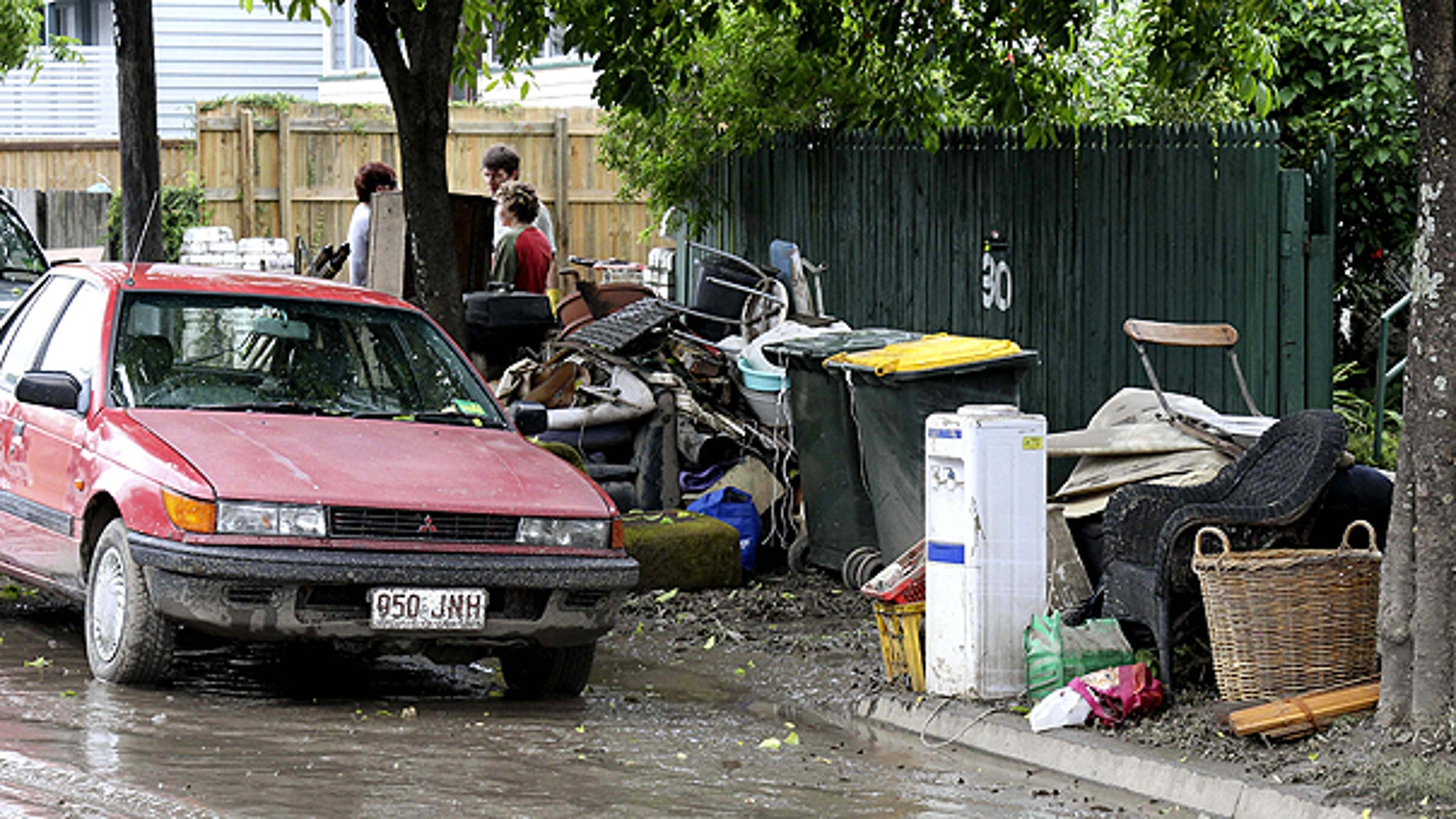 Jan. 14: Damaged goods await removal in front of a flooded home in Brisbane, Australia.