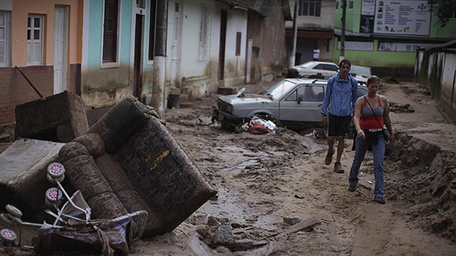 Jan. 15: People walk among debris at a street after landslides in Nova Friburgo, Brazil.