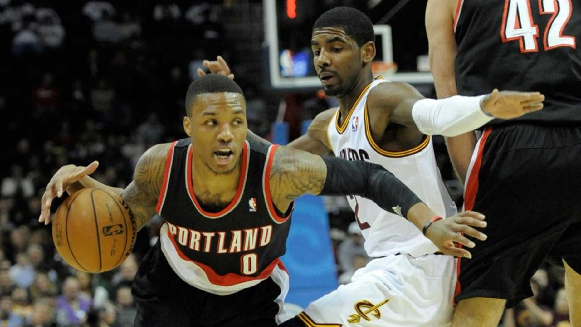 Dec 17, 2013; Cleveland, OH, USA; Cleveland Cavaliers point guard Kyrie Irving (center) works against Portland Trail Blazers point guard Damian Lillard (0) and center Robin Lopez (42) in the first quarter at Quicken Loans Arena. Mandatory Credit: David Richard-USA TODAY Sports