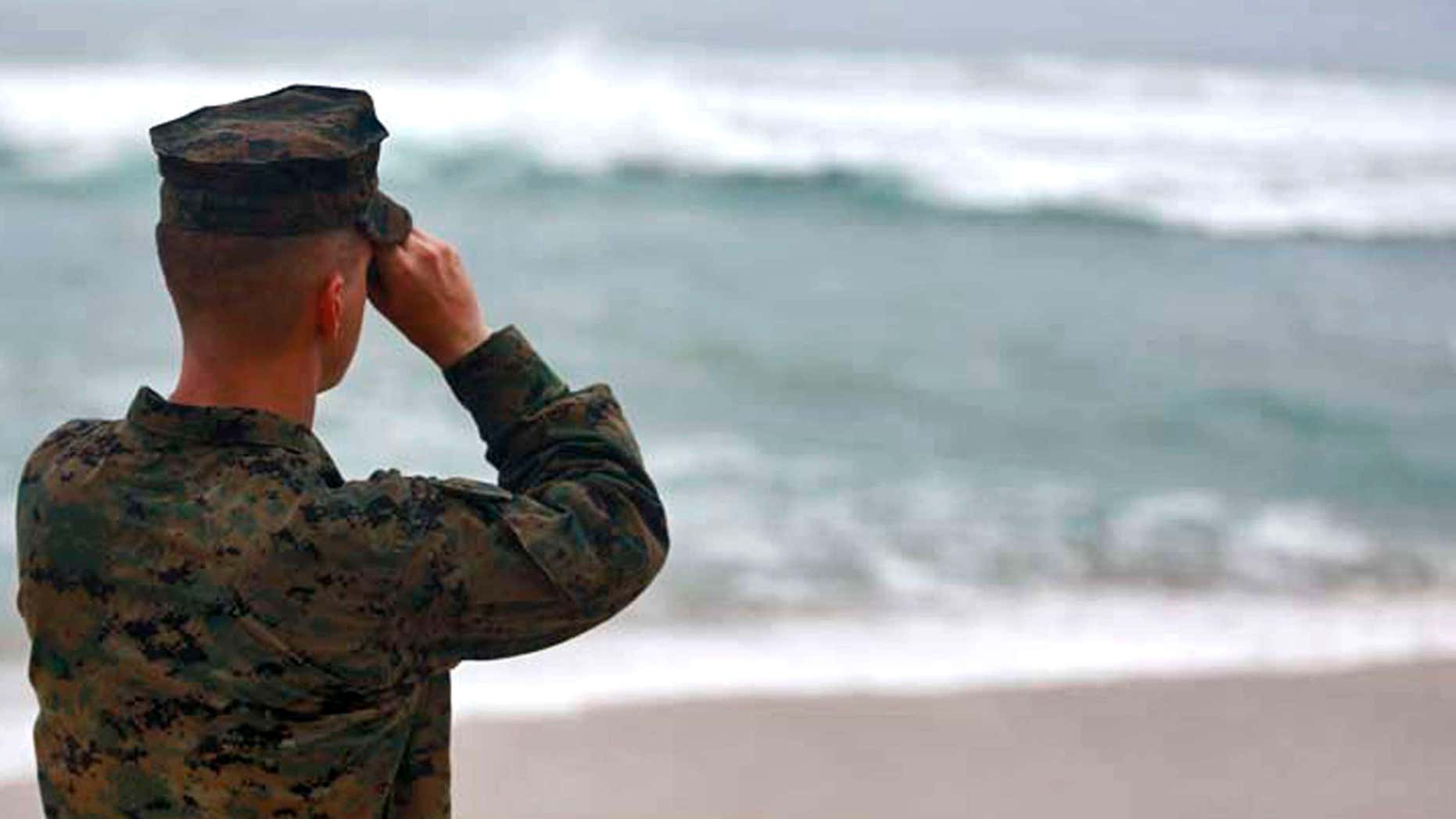 This Friday, Jan. 15, 2016 photo provided by the U.S. Marine Corps shows a Marine Officer attached to Marine Heavy Helicopter Squadron 463 uses binoculars to search for debris of a helicopter mishap in Haliewa Beach Park, Hawaii.