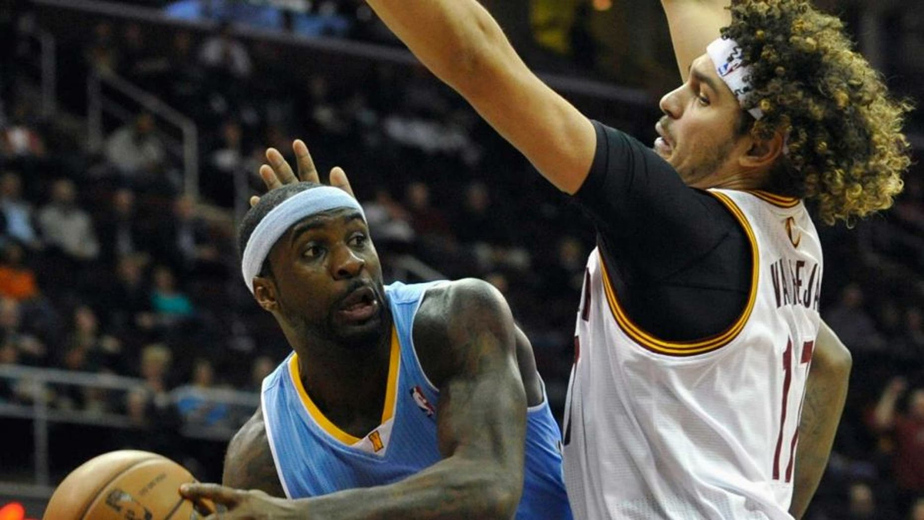 Dec 4, 2013; Cleveland, OH, USA; Denver Nuggets point guard Ty Lawson (3) drives against Cleveland Cavaliers center Anderson Varejao (17) in the first quarter at Quicken Loans Arena. Mandatory Credit: David Richard-USA TODAY Sports