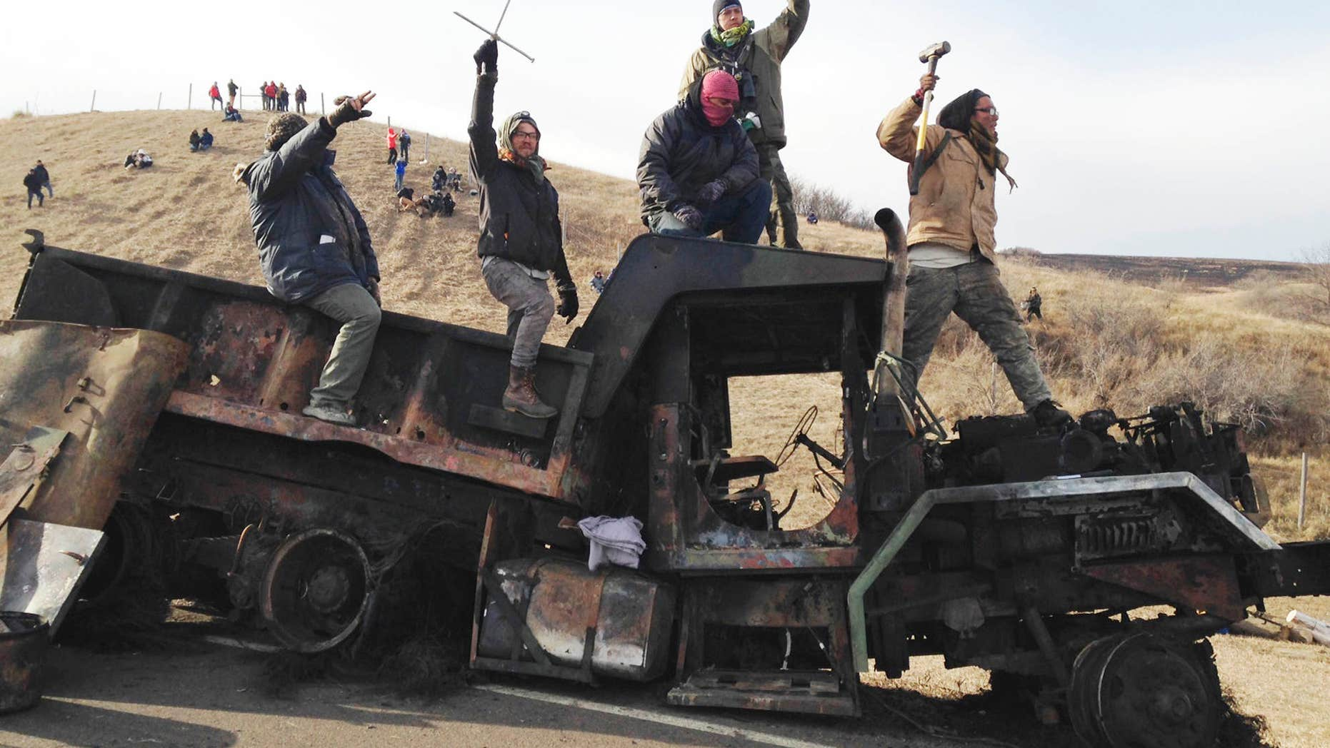 FILE - In this Monday, Nov. 21, 2016, file photo, protesters against the Dakota Access oil pipeline stand on a burned-out truck near Cannon Ball, N.D., that they removed from a long-closed bridge a day earlier on a state highway near their camp.
