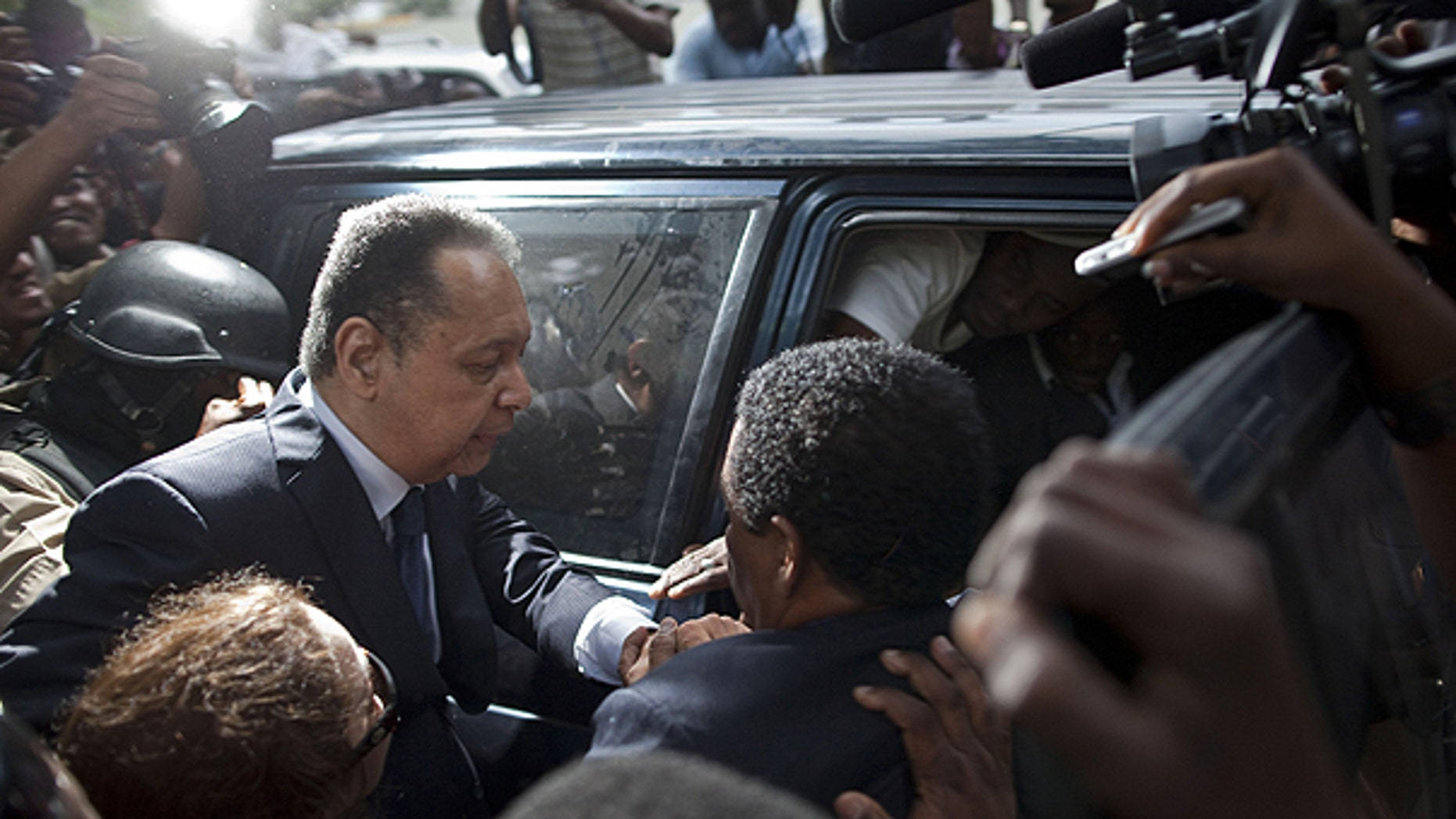Jan. 18: Haiti's former dictator Jean-Claude Duvalier, left, leaves court surrounded by journalists in Port-au-Prince, Haiti.