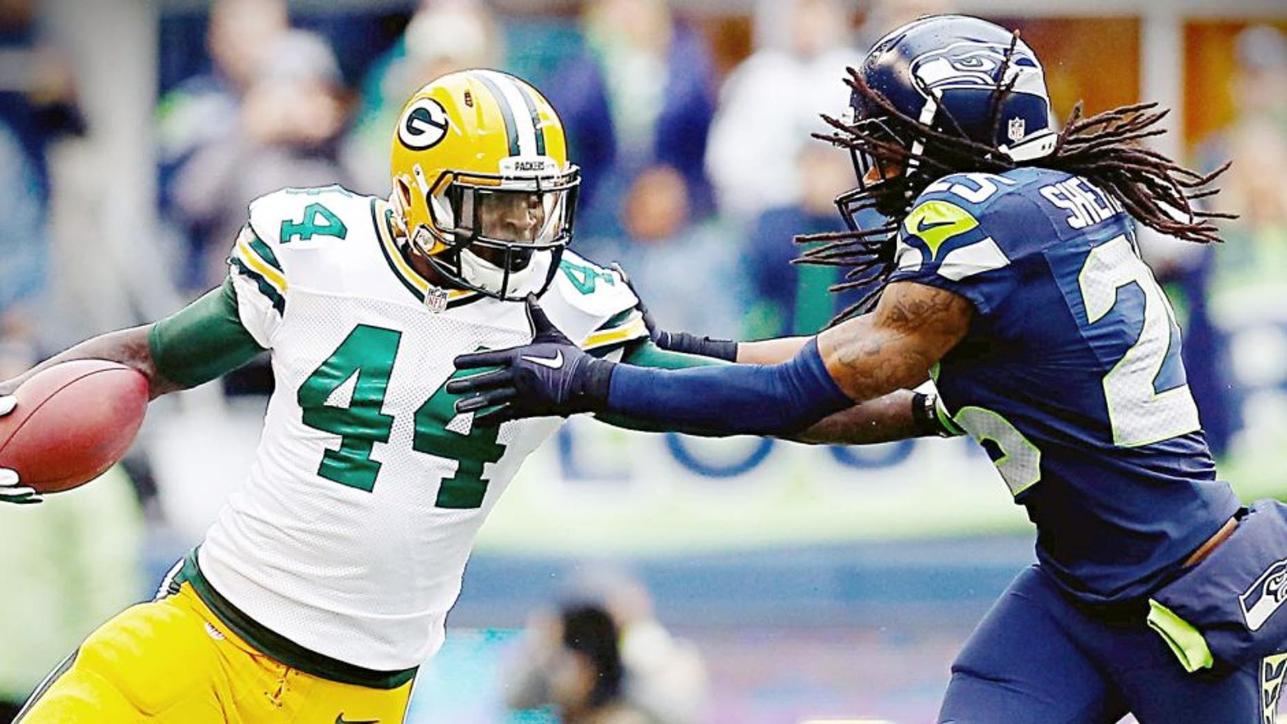 SEATTLE, WA - JANUARY 18: James Starks #44 of the Green Bay Packers gives Richard Sherman #25 of the Seattle Seahawks a stiff arm as he runs with the ball during the second half of the 2015 NFC Championship game at CenturyLink Field on January 18, 2015 in Seattle, Washington. (Photo by Tom Pennington/Getty Images)