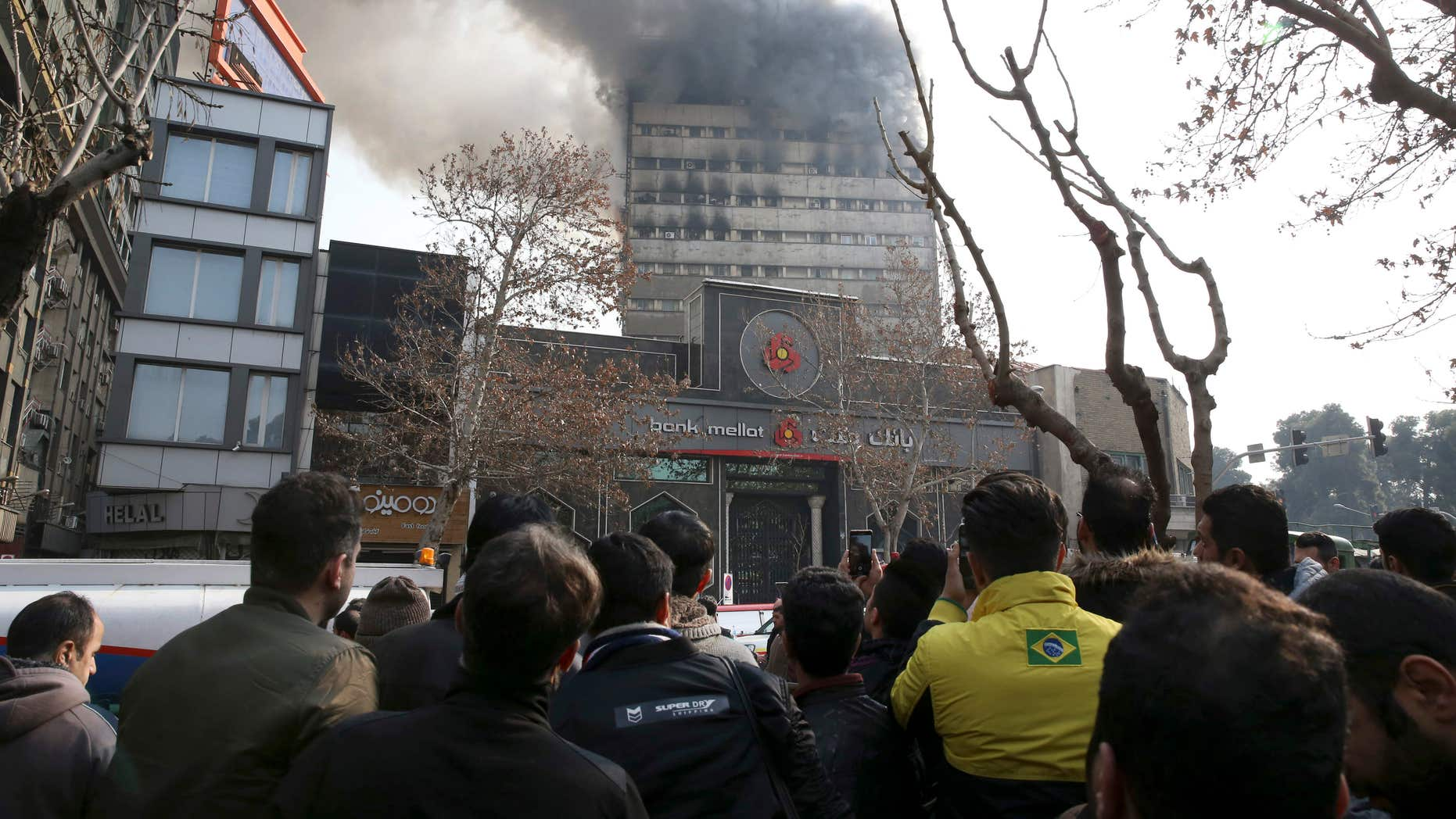 Jan. 19, 2017: Iranians watch the Plasco building where smoke rises from its windows in central Tehran, Iran.