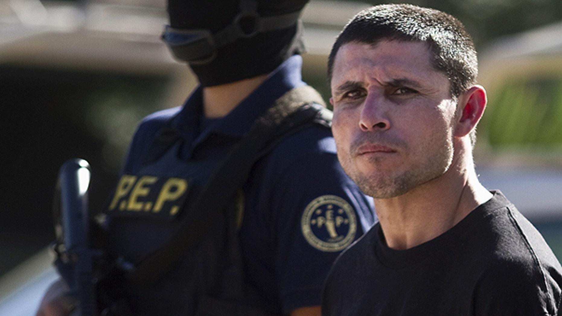 Jan. 20: A suspected member of the Sinaloa drug cartel, Juan Miguel Valle Beltran, right, aka 'El Boxer' is presented to the media in Tijuana, Mexico.