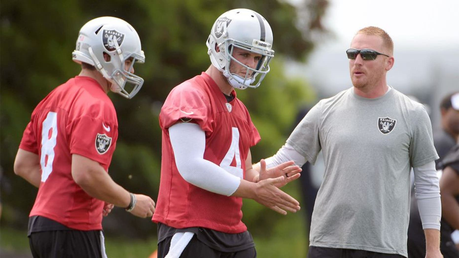 Jun 9, 2015; Oakland, CA, USA; Oakland Raiders quarterbacks coach Todd Downing (right) with quarterbacks Cody Fajardo (8) and Derek Carr (4) at minicamp at the Raiders practice facility. Mandatory Credit: Kirby Lee-USA TODAY Sports